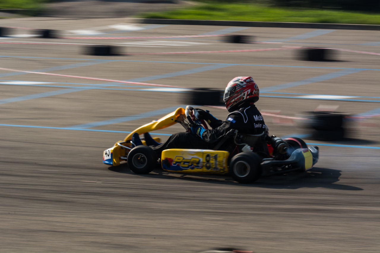 speed, sports race, motorsport, motion, sport, sports track, land vehicle, blurred motion, crash helmet, sports clothing, auto racing, side view, racecar, competition, day, helmet, real people, outdoors