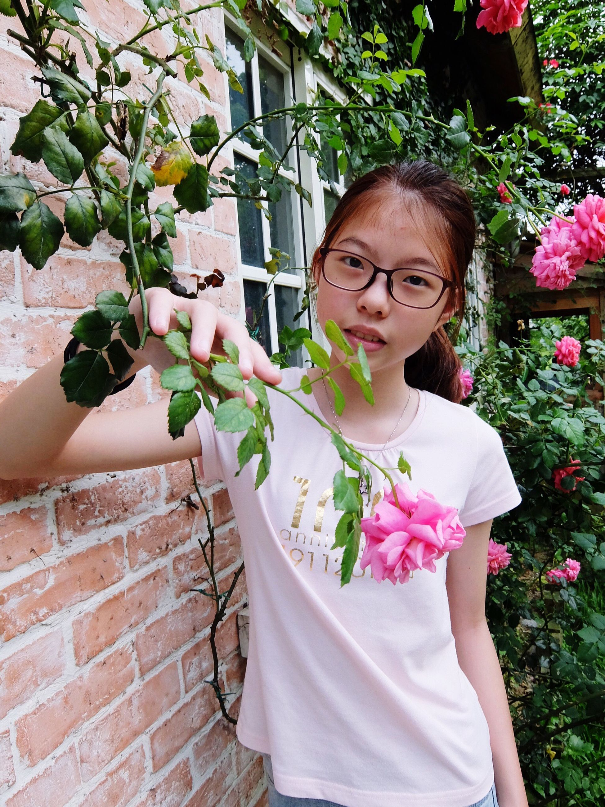 flower, lifestyles, freshness, plant, person, growth, standing, leisure activity, casual clothing, potted plant, pink color, young adult, leaf, holding, young women, fragility, sitting, front view