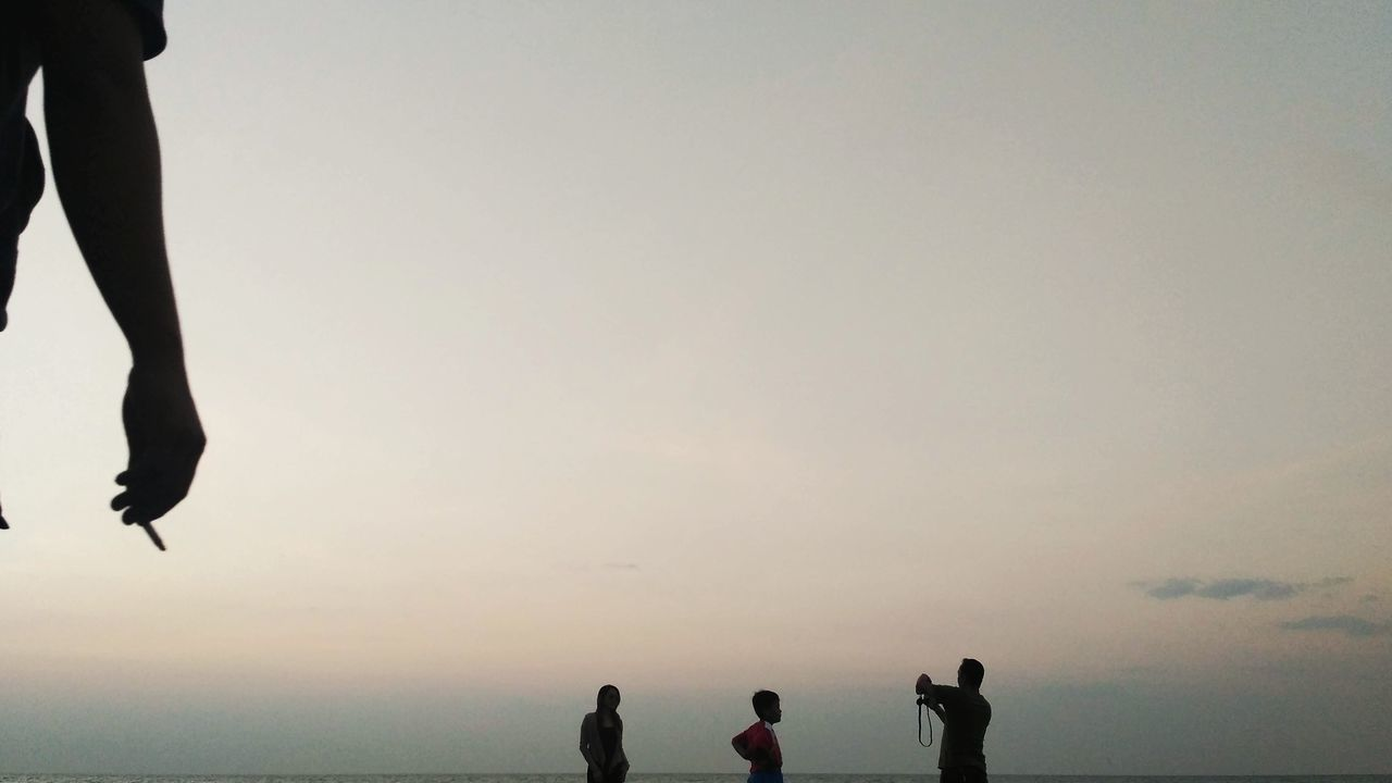 real people, leisure activity, men, silhouette, lifestyles, togetherness, water, sky, outdoors, standing, women, nature, sea, low section, horizon over water, clear sky, boys, sunset, beauty in nature, childhood, day, friendship, adult, people