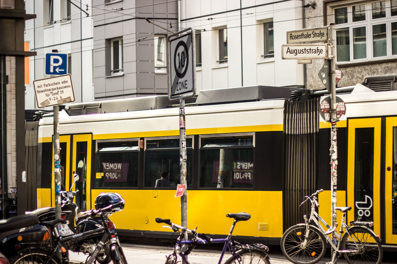 mode of transport, transportation, land vehicle, built structure, building exterior, architecture, yellow, outdoors, stationary, day, no people, city