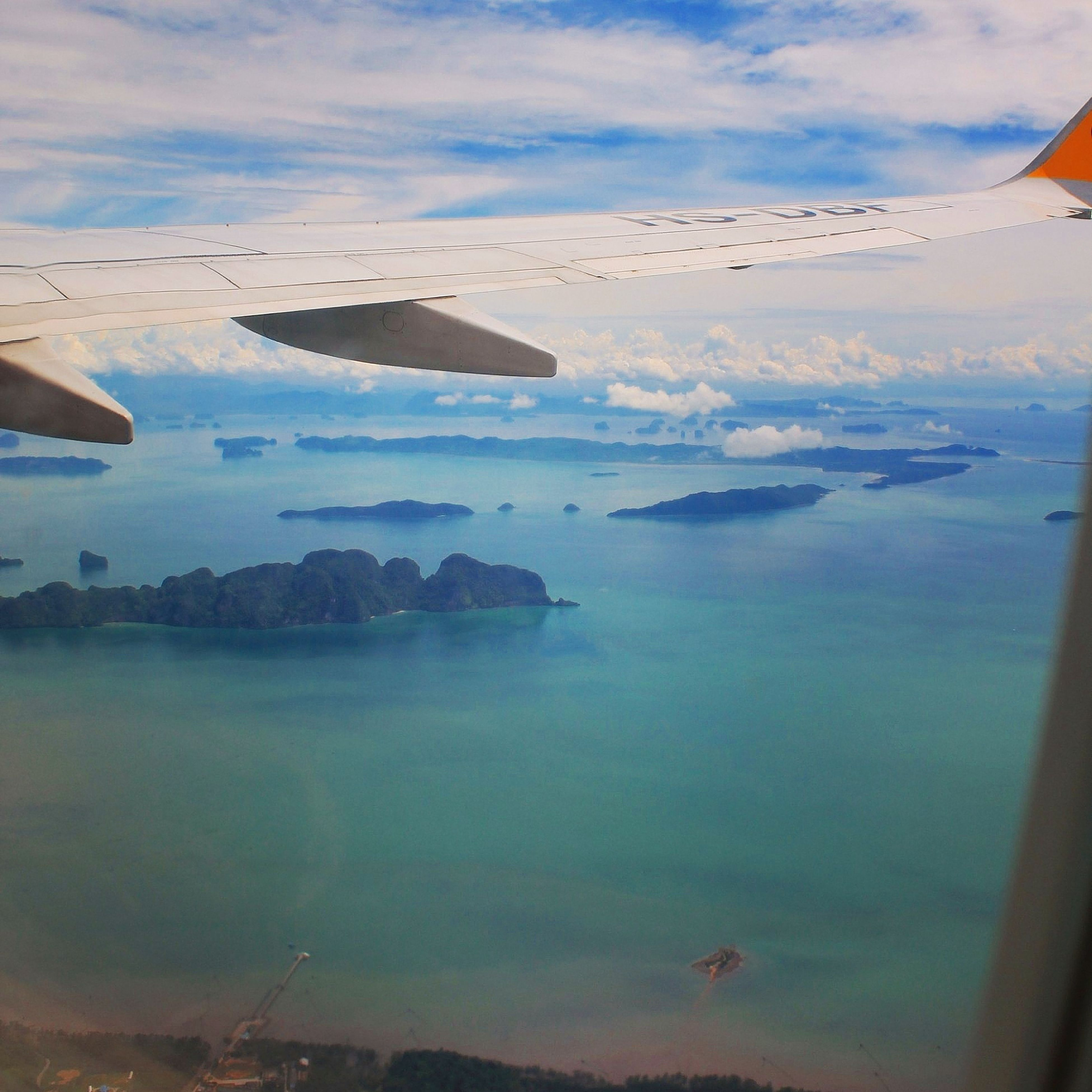 flying, transportation, mode of transport, airplane, air vehicle, sea, sky, mid-air, water, aerial view, aircraft wing, cloud - sky, scenics, travel, part of, nature, beauty in nature, cropped, cloud, nautical vessel