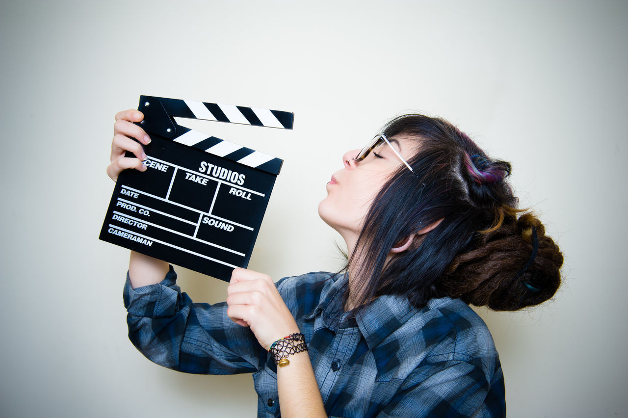 Young pretty teen woman with movie clapper board Actress Alternative Audition Cheerful Clapper Clapperboard Eyeglasses  Film Industry Girl Happy Hypster Kissing MOVIE One Person One Young Woman Only People Pretty Smiling Studio Shot Teen Wolf Teenager Young Young Woman