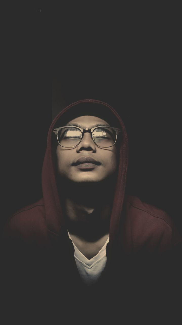 studio shot, black background, eyeglasses, young adult, one person, human face, indoors, close-up