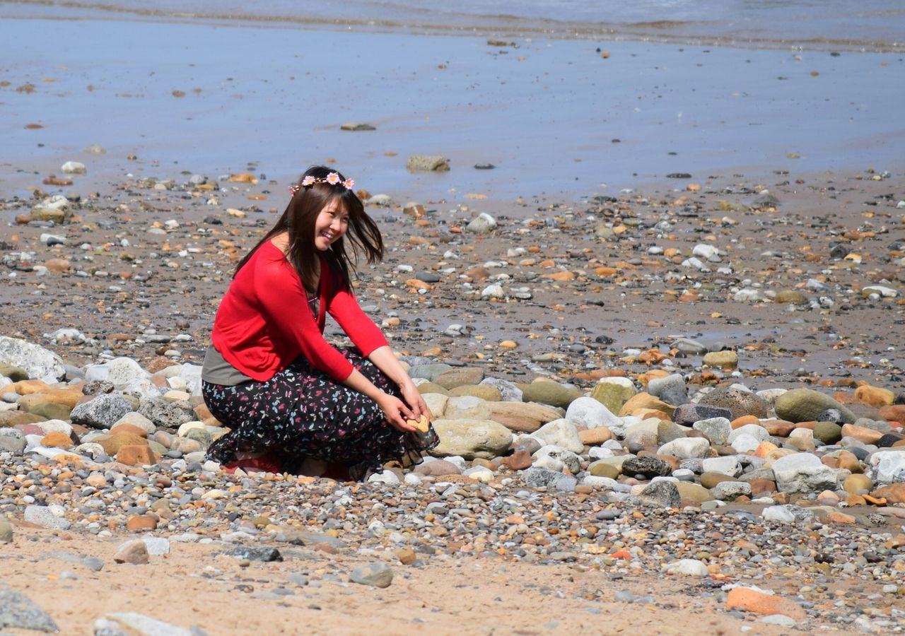 beach, shore, sand, sea, one person, outdoors, real people, pebble, rock - object, nature, water, long hair, day, vacations, young adult, young women, full length, standing, beautiful woman, beauty in nature, sky, adult, people