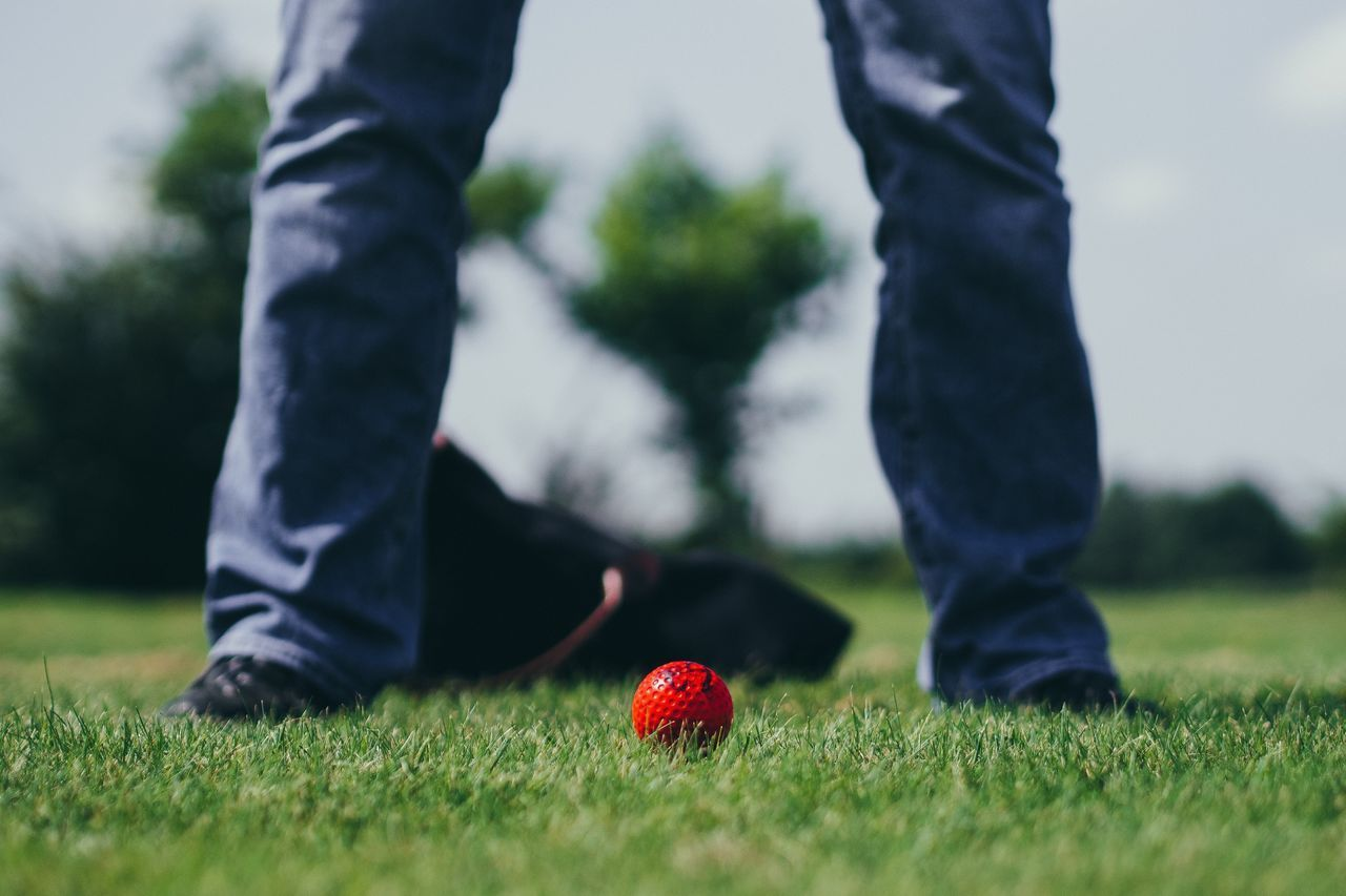 Low Section Of Man Standing On Grassy Field By Golf Ball