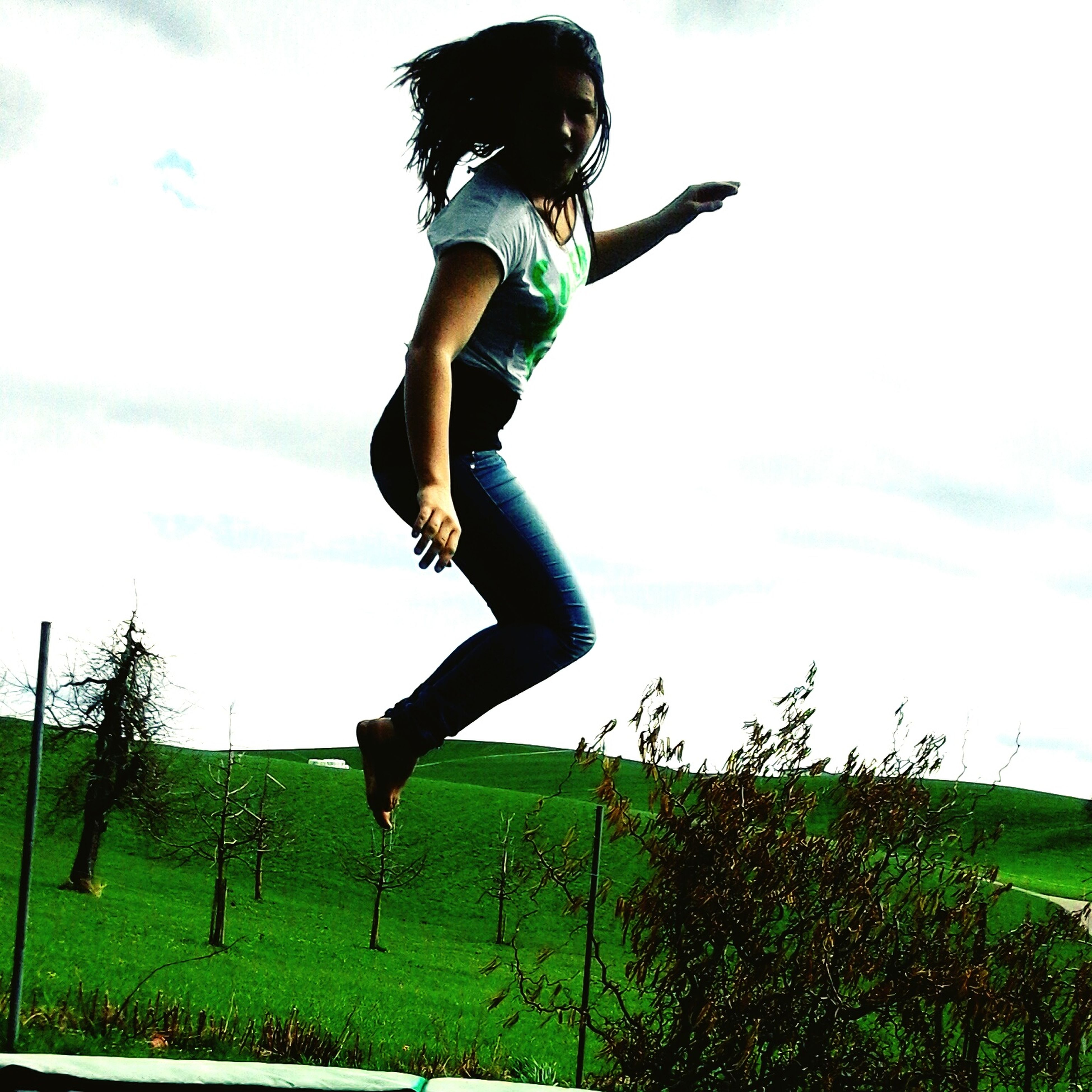 full length, grass, mid-air, lifestyles, leisure activity, jumping, arms outstretched, sky, casual clothing, freedom, field, enjoyment, fun, grassy, arms raised, vitality, carefree, young adult