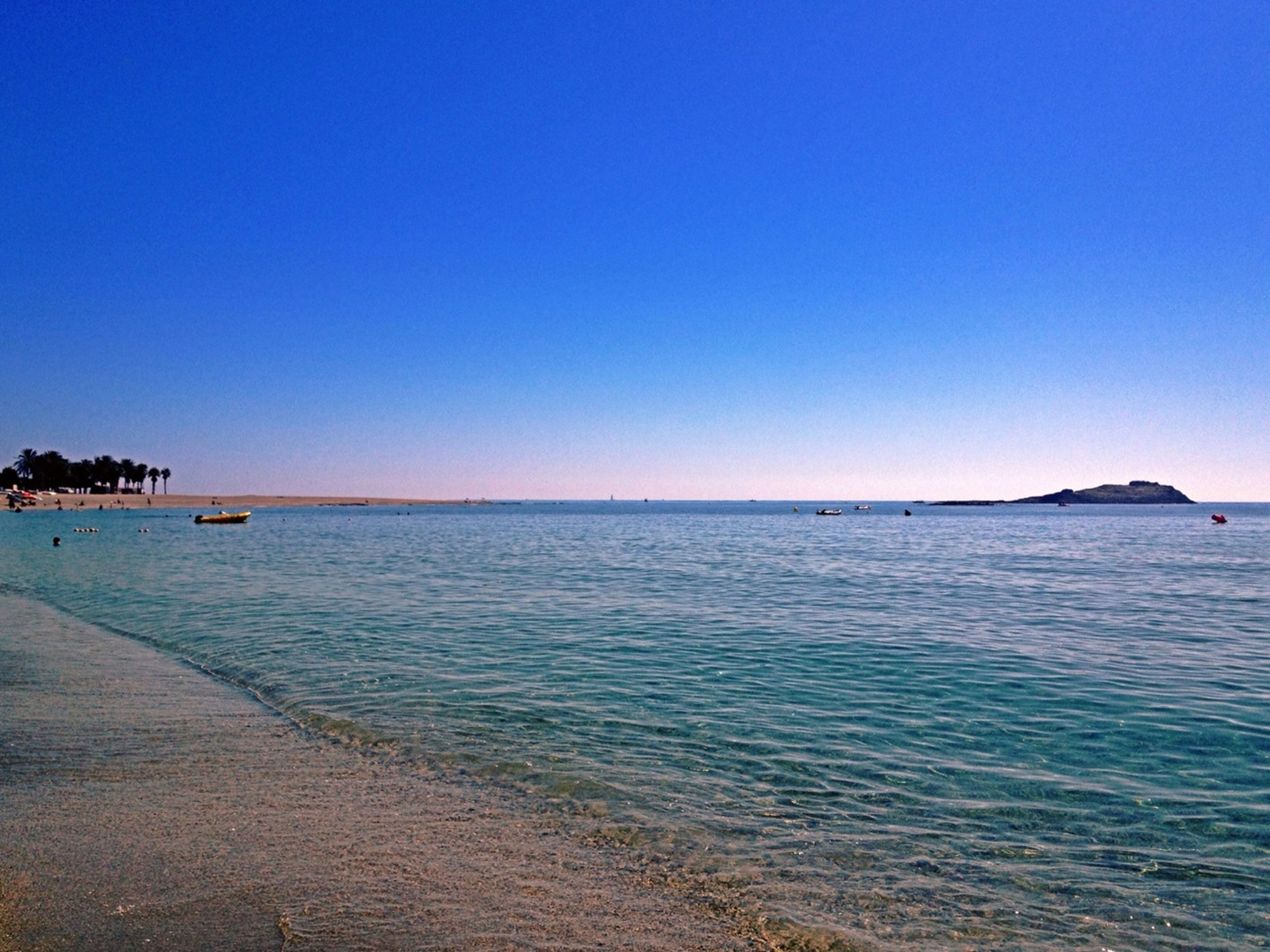 sea, water, clear sky, copy space, blue, tranquil scene, horizon over water, tranquility, scenics, beach, beauty in nature, nature, idyllic, shore, rippled, incidental people, waterfront, coastline, seascape, outdoors