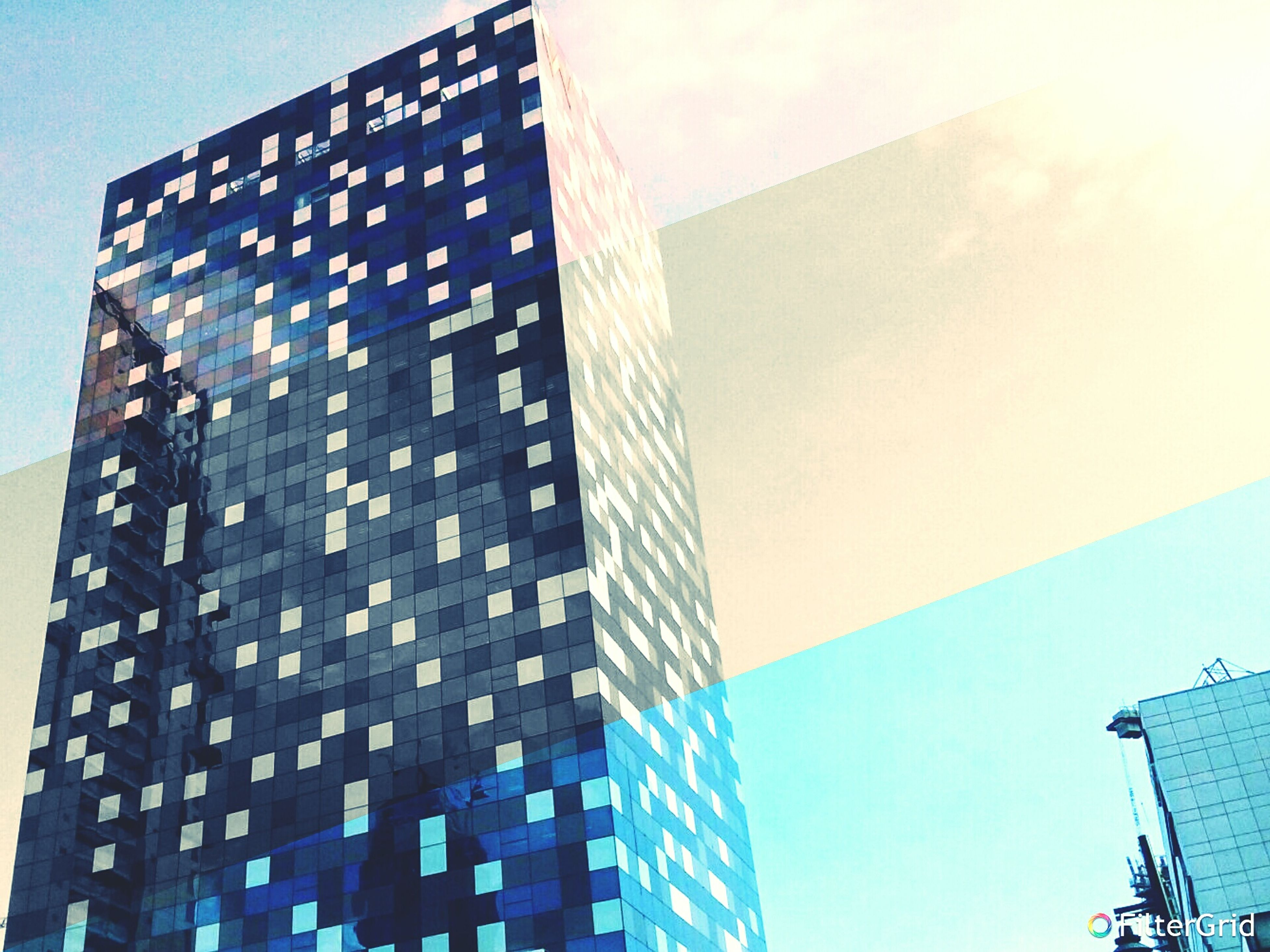 low angle view, architecture, built structure, building exterior, tall - high, skyscraper, modern, office building, city, tower, sky, glass - material, building, development, tall, clear sky, blue, reflection, day, outdoors