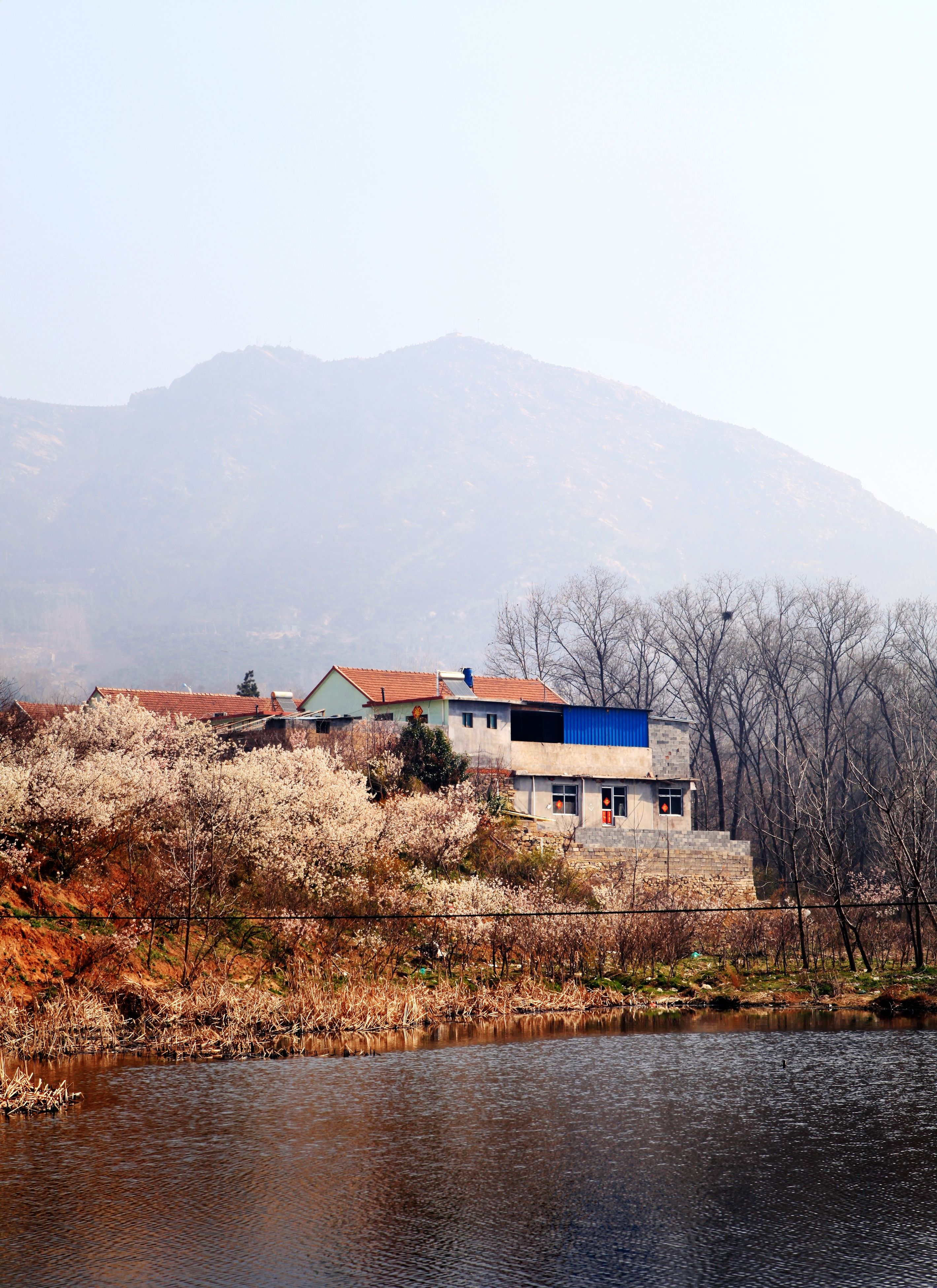 mountain, building exterior, built structure, architecture, house, clear sky, water, sky, nature, tranquil scene, tranquility, copy space, weather, tree, beauty in nature, scenics, day, season, residential structure, landscape