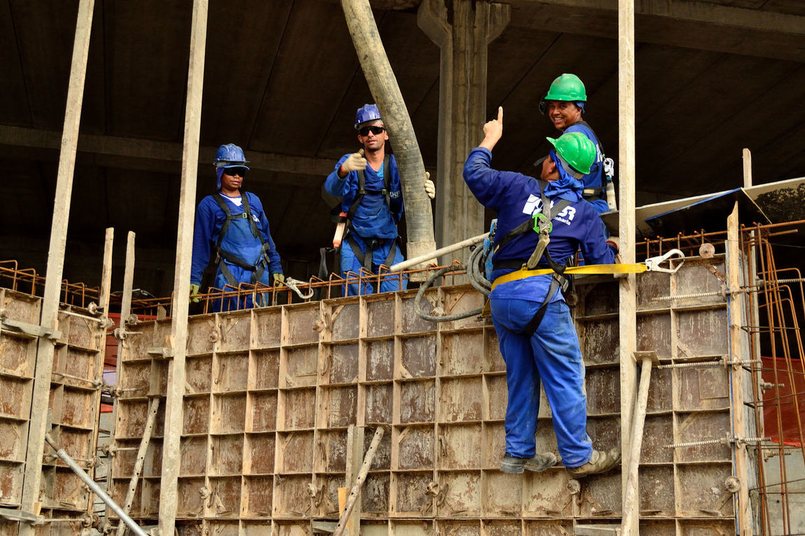 Adventure Architecture Built Structure Coveralls Danger Day Full Length Happiness Hardhat  Headwear Helmet Looking At Camera Manual Worker Mid Adult Mid Adult Men Occupation Outdoors Portrait Protective Workwear Real People Standing Togetherness Working Young Adult Young Women