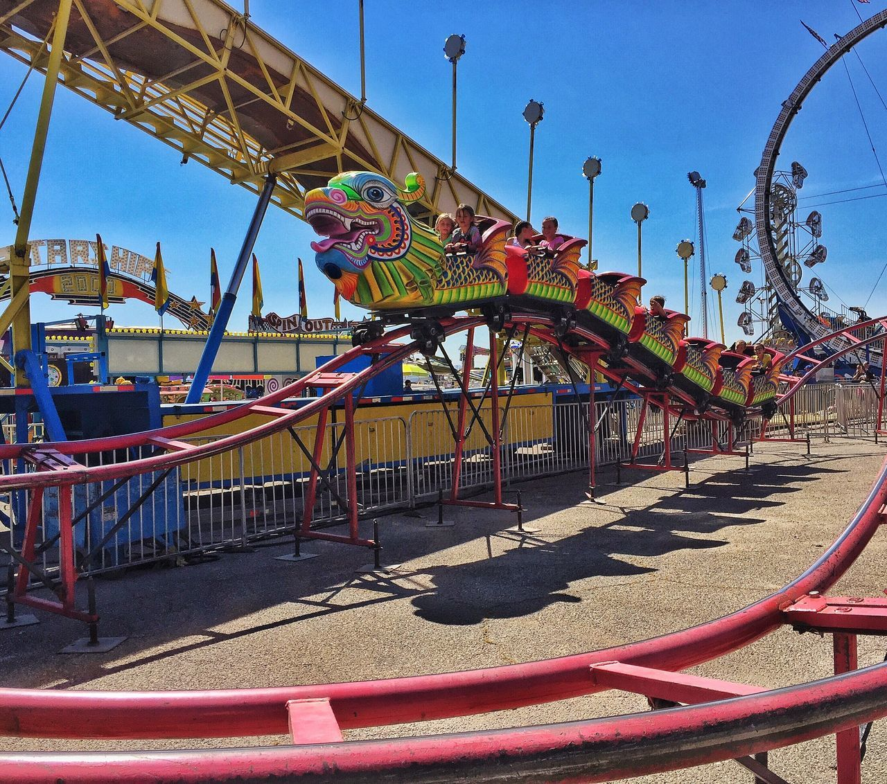 amusement park, arts culture and entertainment, amusement park ride, day, outdoors, fun, leisure activity, clear sky, multi colored, carousel, sunlight, sky, outdoor play equipment, built structure, merry-go-round, no people, nature