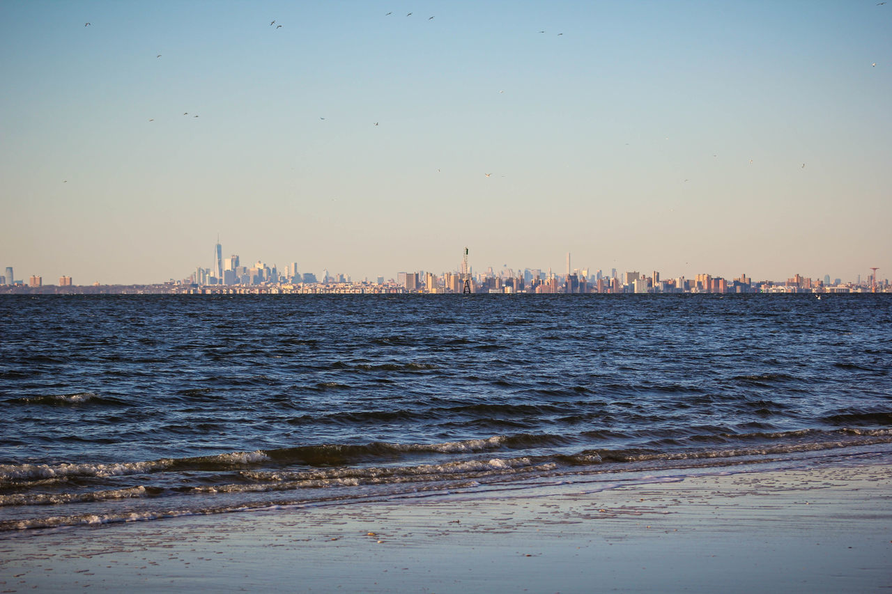 water, city, cityscape, skyscraper, architecture, sea, building exterior, built structure, waterfront, sky, sunset, no people, outdoors, urban skyline, beach, clear sky, nature, day