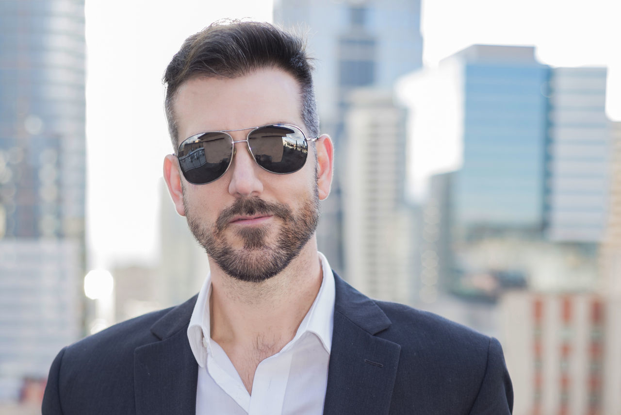 Handsome man wearing sunglasses in the city Architecture Beard Bearded Building Exterior Built Structure Businessman City Close-up Day Focus On Foreground Front View Handsome Headshot Human Looking At Camera Mirrored One Person Outdoors Portrait Professional Real People Sunglasses Young Adult Young Men