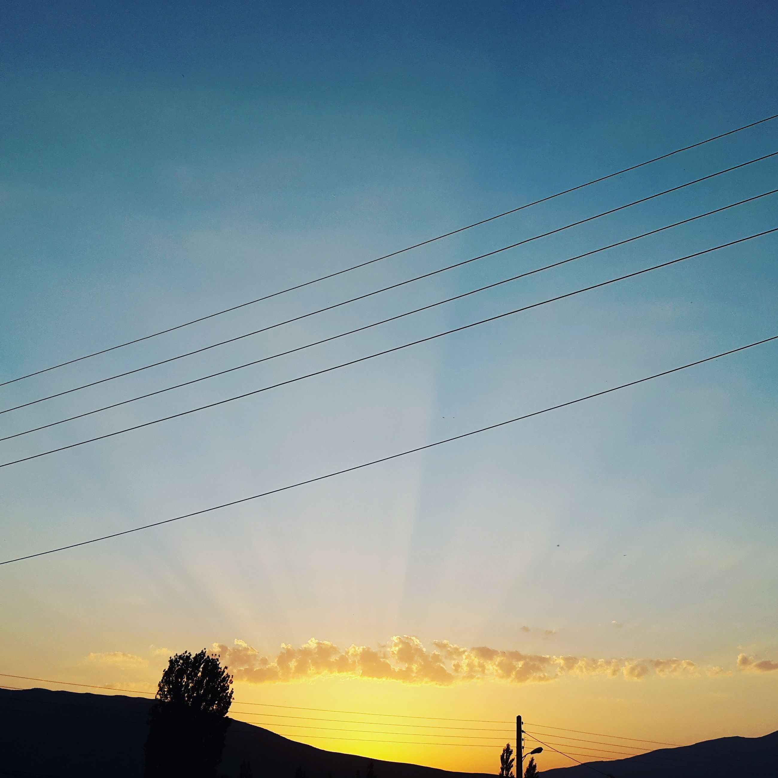 silhouette, sunset, low angle view, sky, power line, beauty in nature, nature, tranquility, scenics, tranquil scene, outdoors, cable, no people, orange color, cloud - sky, outline, cloud, blue, idyllic, high section, power supply