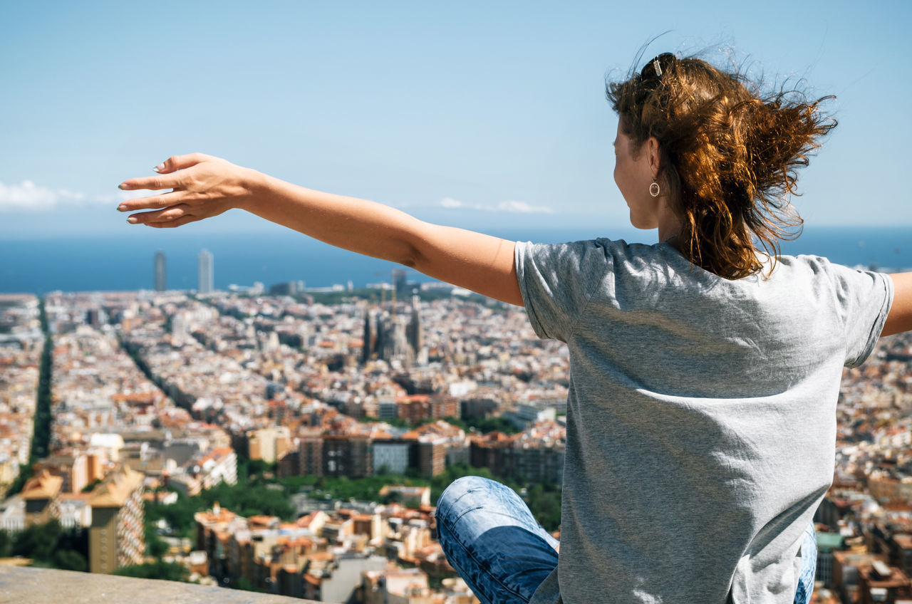 Young happy woman sits back to the camera with raised hands. Traveler enjoying the cityscape of mountain, Barcelona, Catalonia, Spain Architecture Barcelona Building Exterior Catalunya City Cityscape Clear Sky Close-up Hands Leisure Activity One Woman Only Outdoors Roof Sky SPAIN Tourist Urban Skyline Vacations Young Adult Young Women
