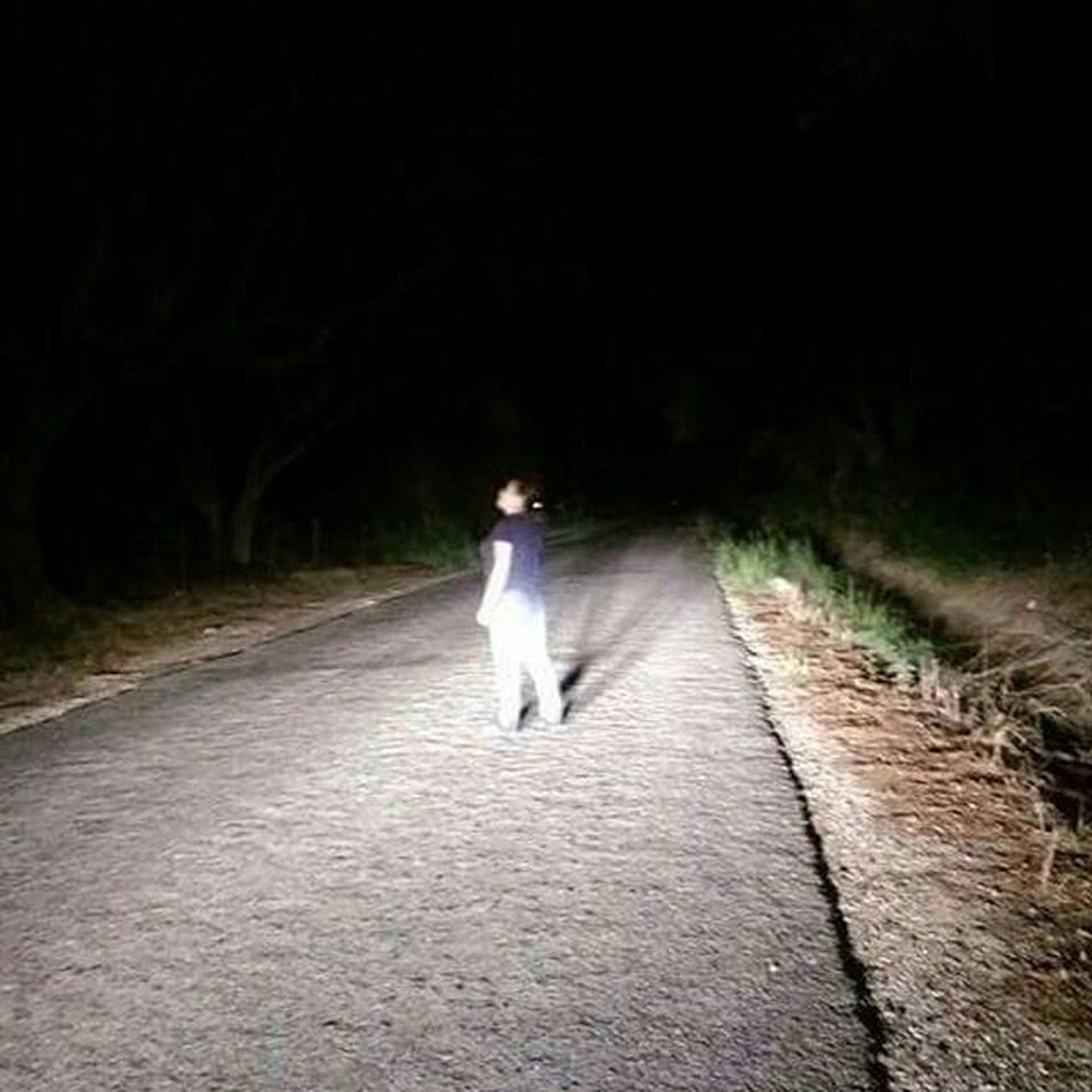 full length, lifestyles, rear view, walking, the way forward, night, casual clothing, standing, leisure activity, road, front view, street, diminishing perspective, vanishing point, person, young adult, illuminated, outdoors