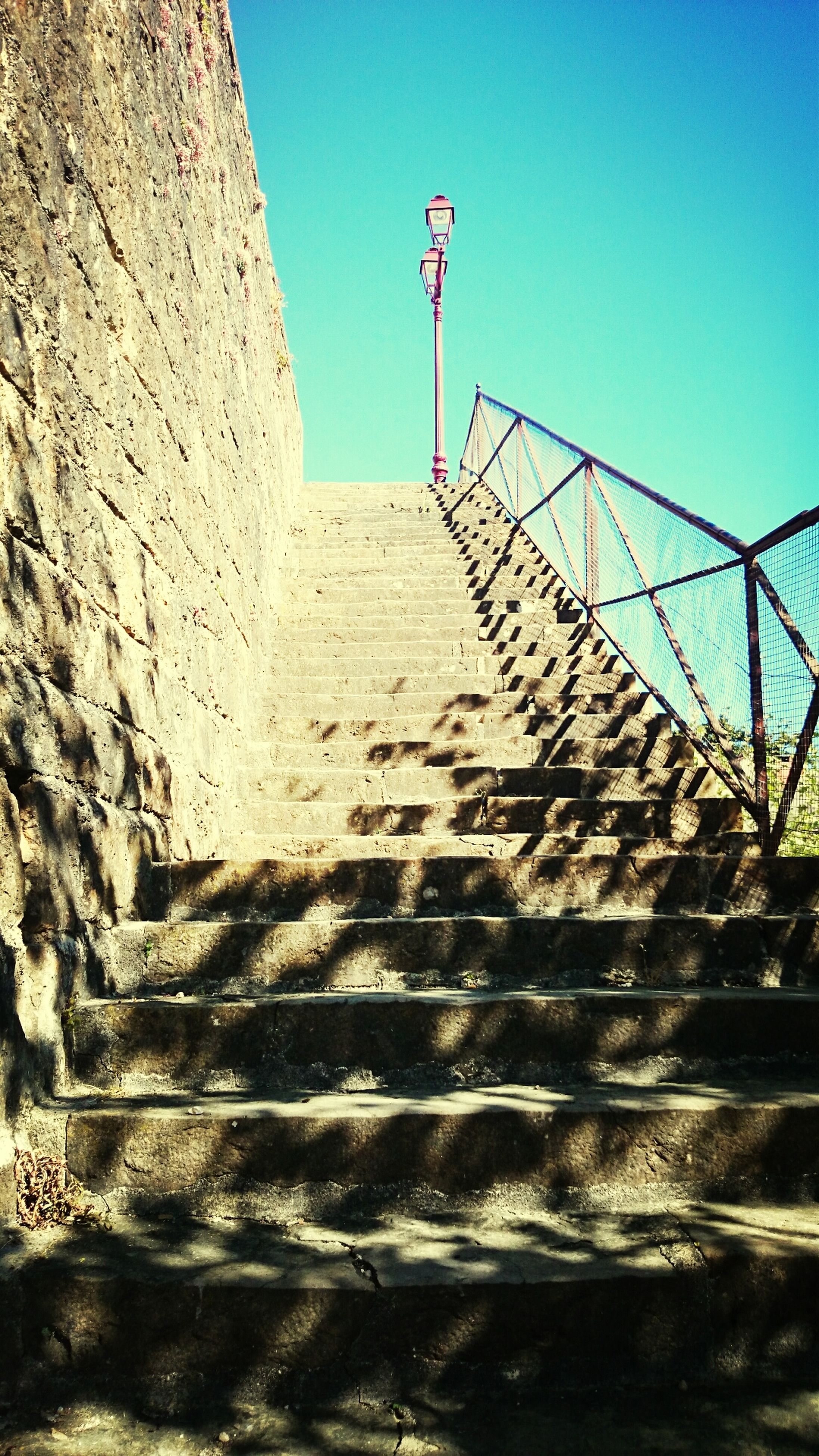 clear sky, built structure, architecture, sunlight, blue, steps, the way forward, railing, steps and staircases, shadow, staircase, day, sea, sky, copy space, building exterior, low angle view, outdoors, sunny, no people