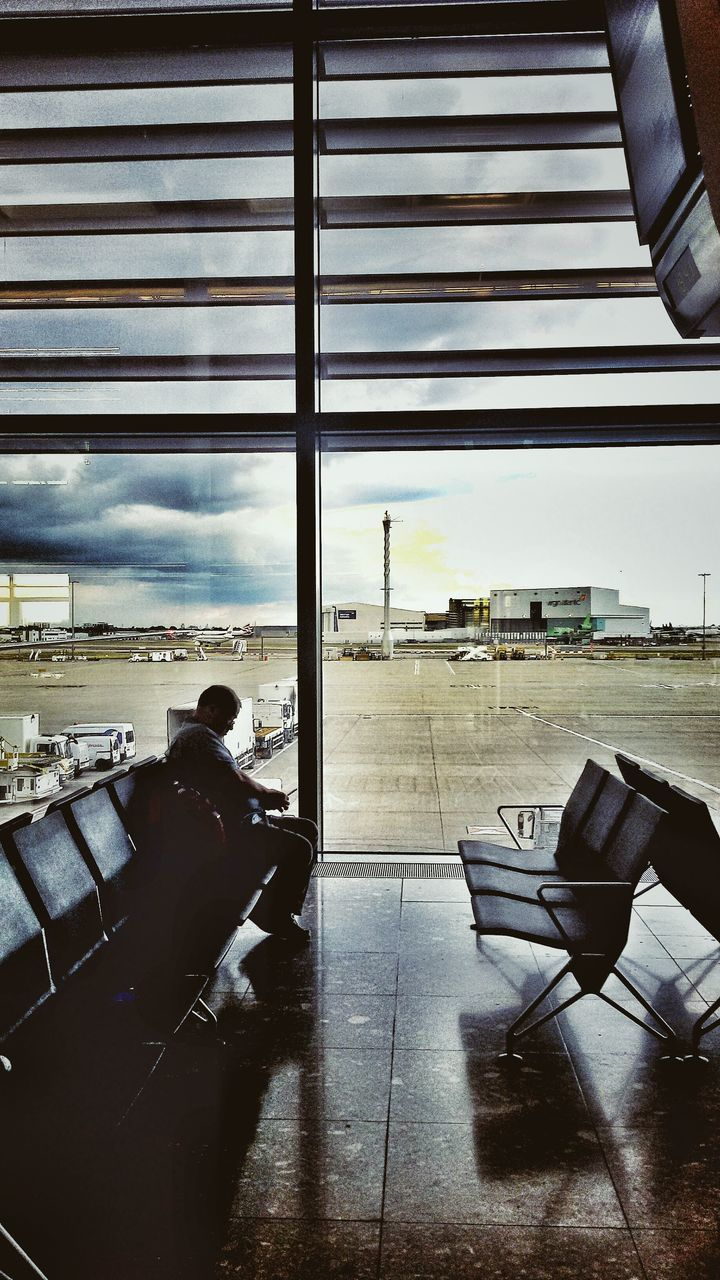 airport, indoors, window, airplane, travel, airport departure area, transportation, day, air vehicle, men, one person, real people, architecture, luggage, sky, runway, flying, commercial airplane, human hand, people