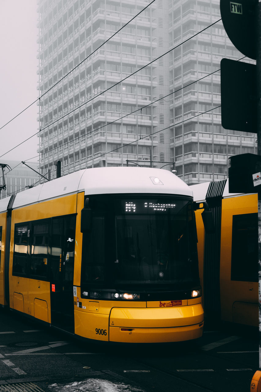 transportation, mode of transport, public transportation, architecture, built structure, yellow, day, land vehicle, building exterior, city, train - vehicle, outdoors, no people