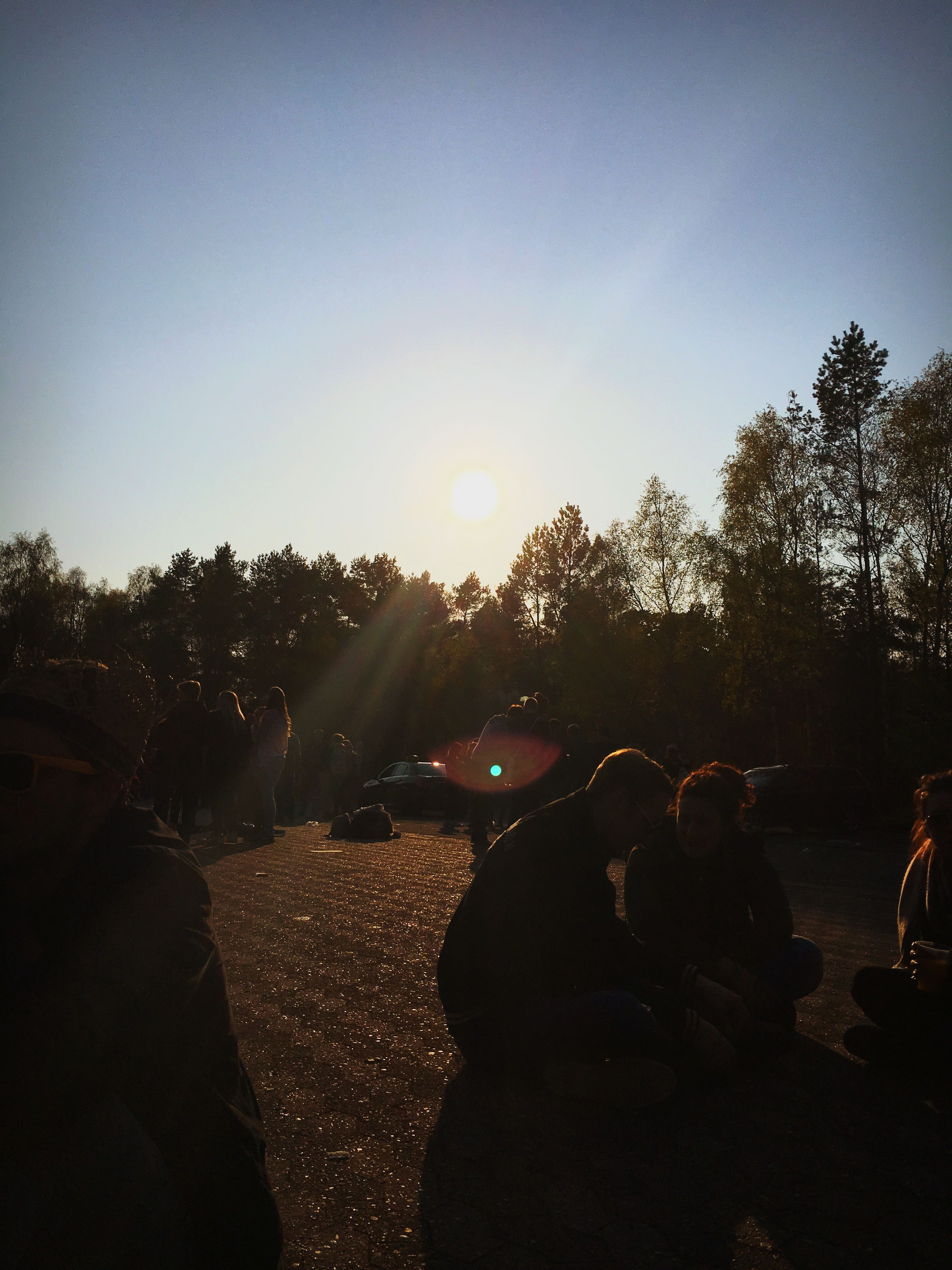 silhouette, sunset, tree, lifestyles, men, sun, leisure activity, sky, lens flare, clear sky, sunlight, large group of people, sunbeam, person, land vehicle, unrecognizable person, car, transportation, outdoors