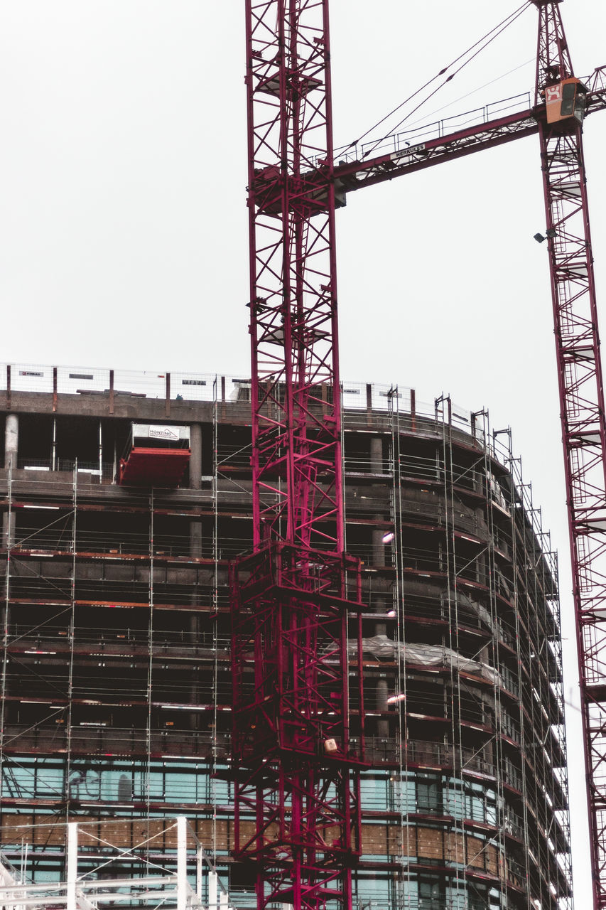 construction site, construction, architecture, development, built structure, red, low angle view, industry, clear sky, building exterior, day, building - activity, outdoors, progress, no people, sky