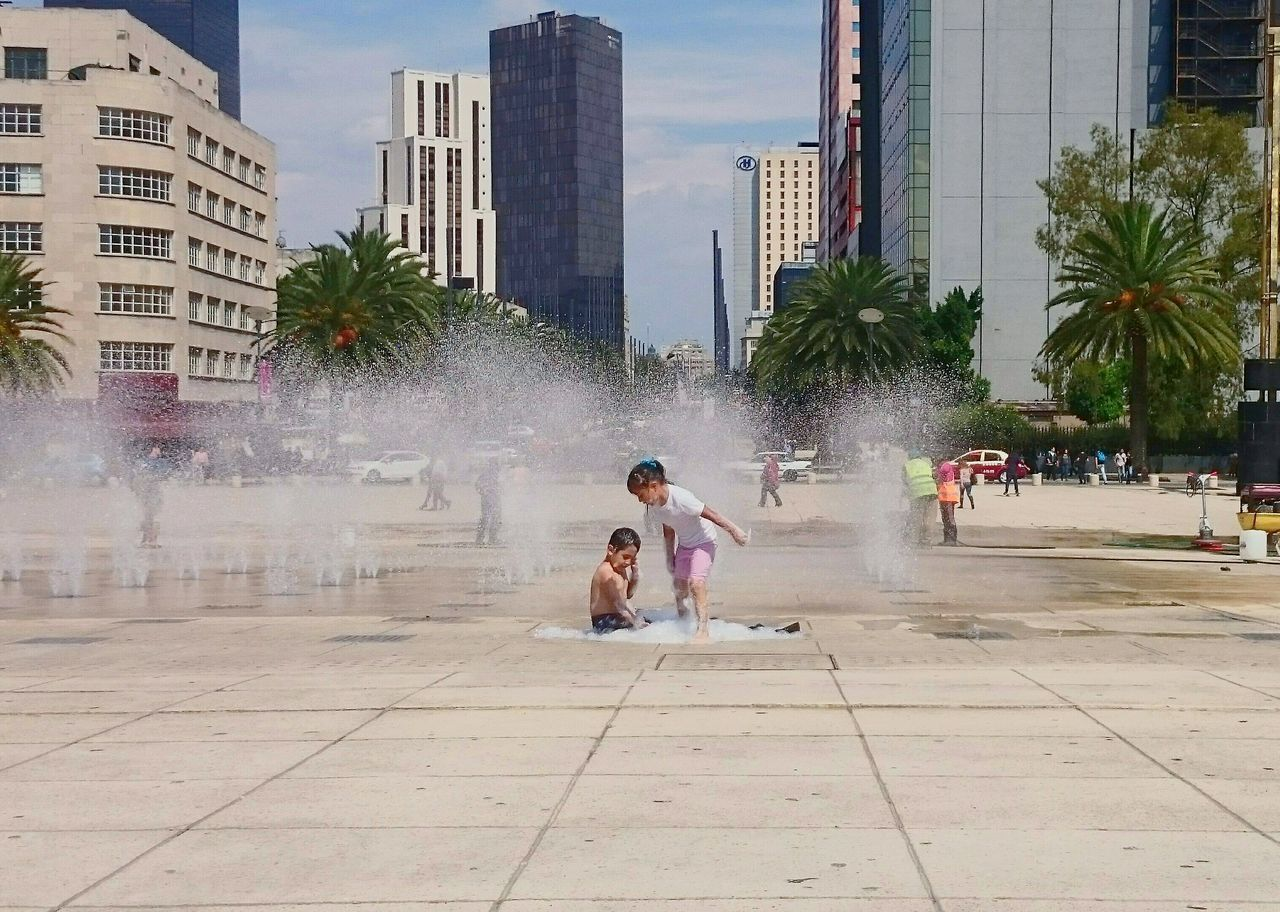 Siblings Enjoying Fountain At Town Square In City