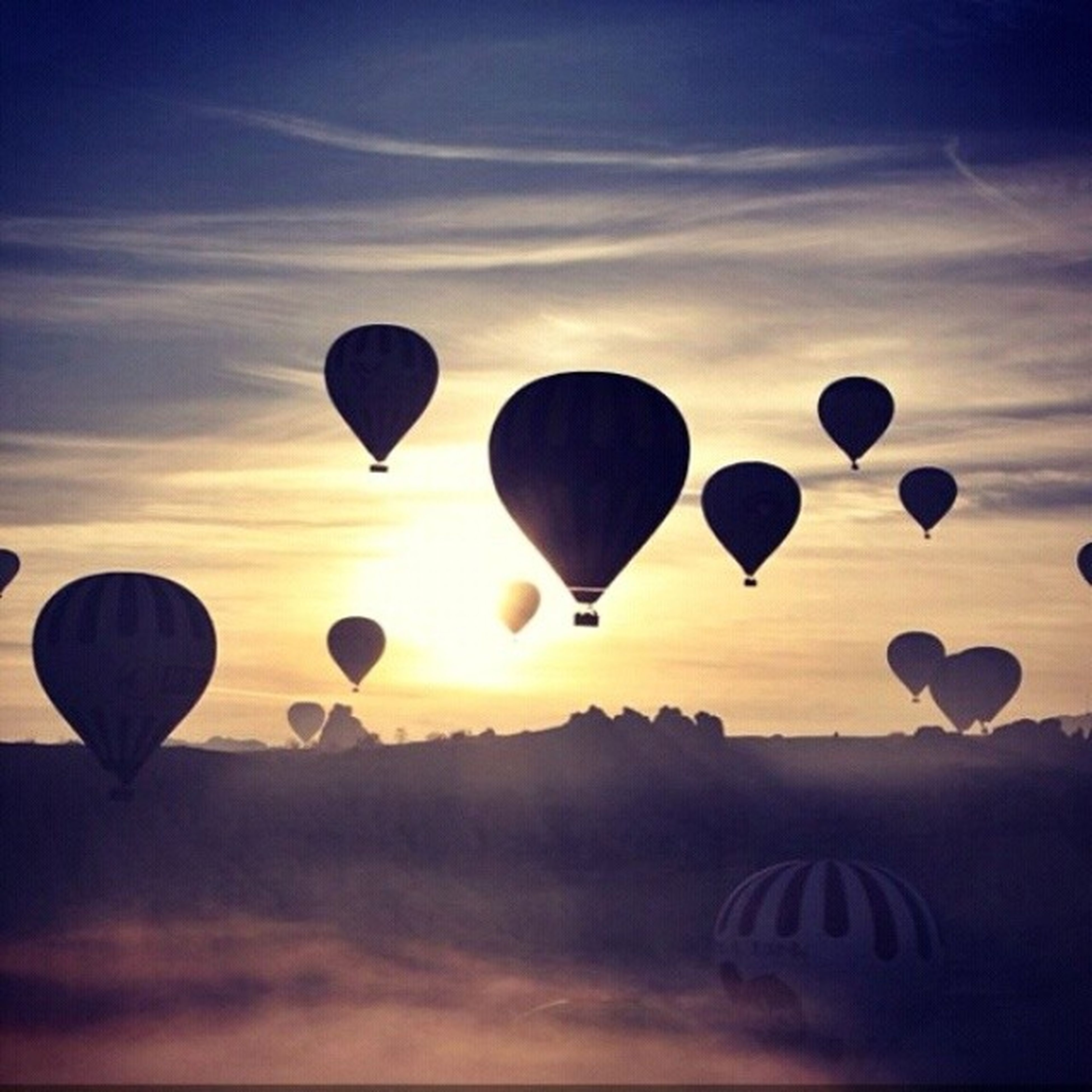 hot air balloon, flying, mid-air, sky, parachute, sunset, multi colored, low angle view, cloud - sky, scenics, silhouette, tranquility, balloon, transportation, tranquil scene, adventure, nature, beauty in nature, outdoors, circle
