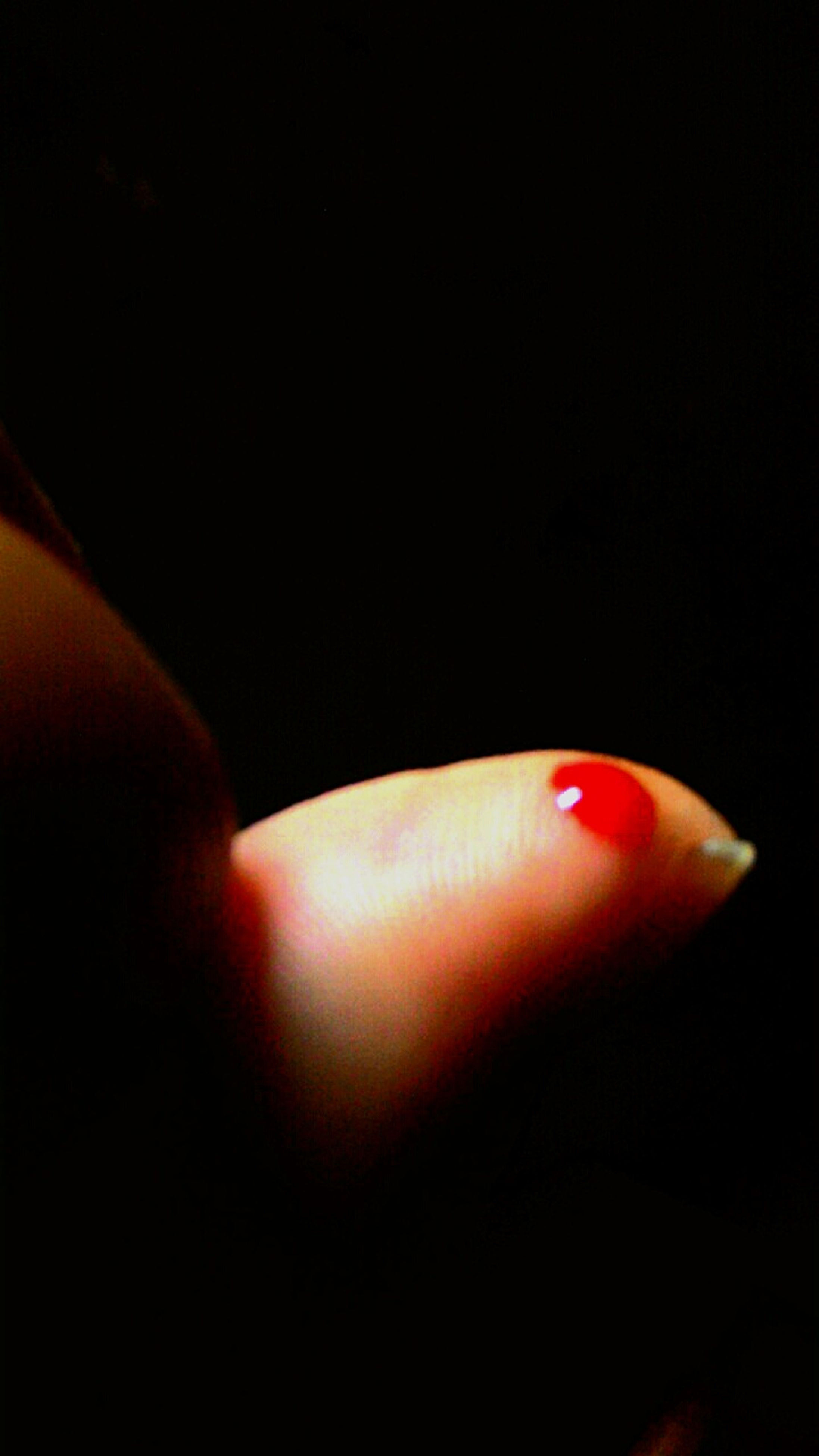 person, part of, human finger, cropped, holding, red, unrecognizable person, personal perspective, close-up, lifestyles, indoors, copy space, black background, studio shot, leisure activity, nail polish