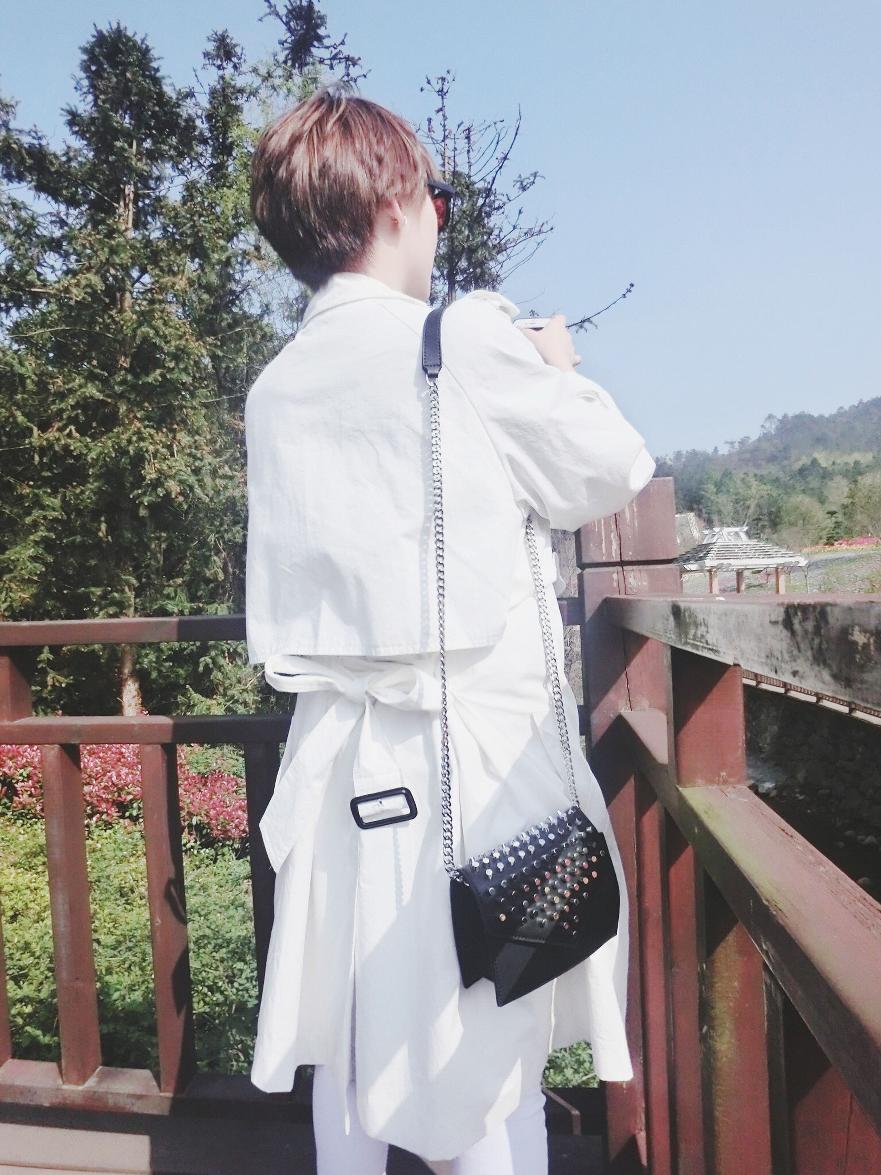 casual clothing, lifestyles, tree, leisure activity, person, standing, three quarter length, young adult, railing, full length, front view, waist up, sitting, holding, day, focus on foreground, outdoors, sunlight
