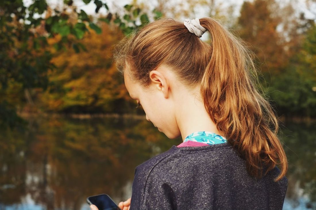 Young girl using social network on smart phone while beeing in nature Real People Headshot One Person Focus On Foreground Leisure Activity Lifestyles Outdoors Day Nature Close-up Hair Bun Young Adult Young Women Tree Smartphone Social Networking Isolation Communication Authentic Moments