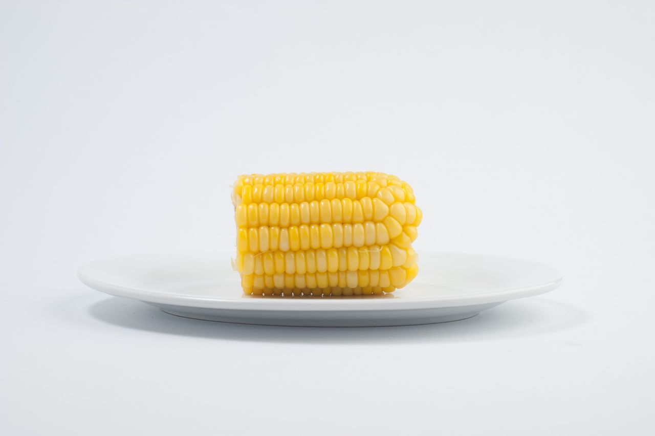 Close-Up Of Corn In Plate Against White Background