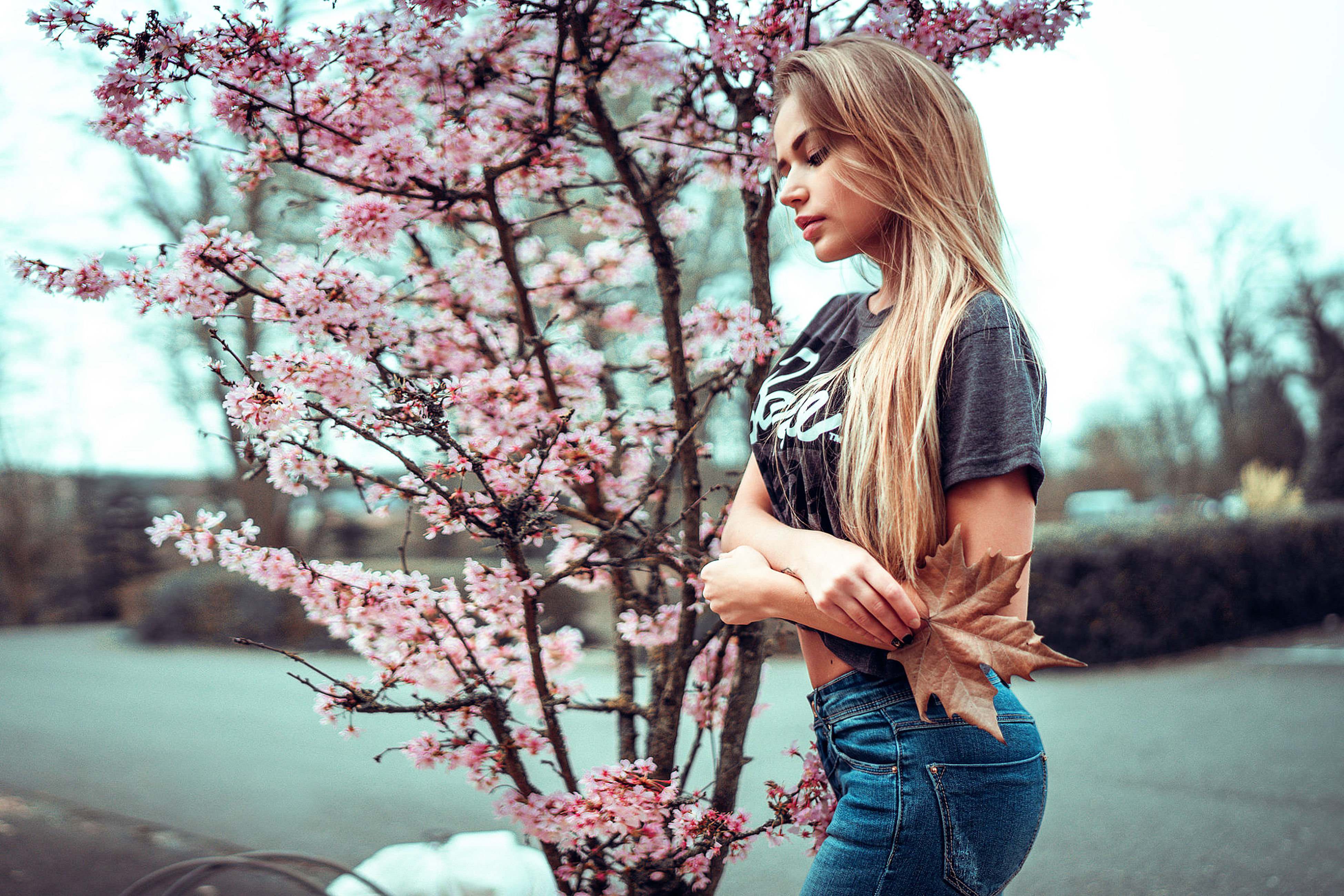 flower, tree, one person, nature, blossom, casual clothing, beauty in nature, young adult, springtime, day, real people, young women, outdoors, standing, beautiful woman, side view, leisure activity, long hair, fragility, focus on foreground, branch, blond hair, growth, one young woman only, women, lifestyles, freshness, sky, people