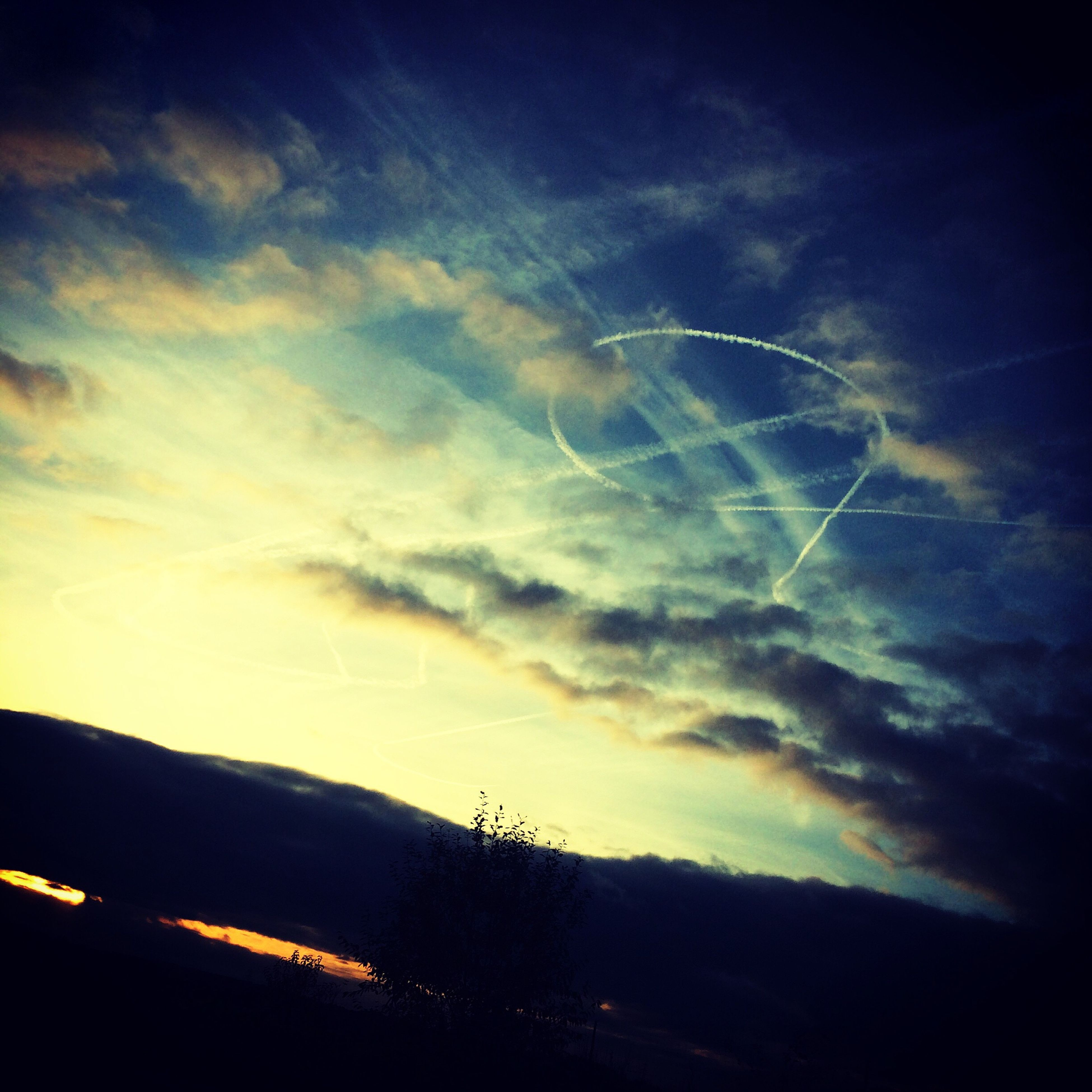 sky, low angle view, silhouette, vapor trail, sunset, nature, no people, scenics, outdoors, beauty in nature, day, contrail
