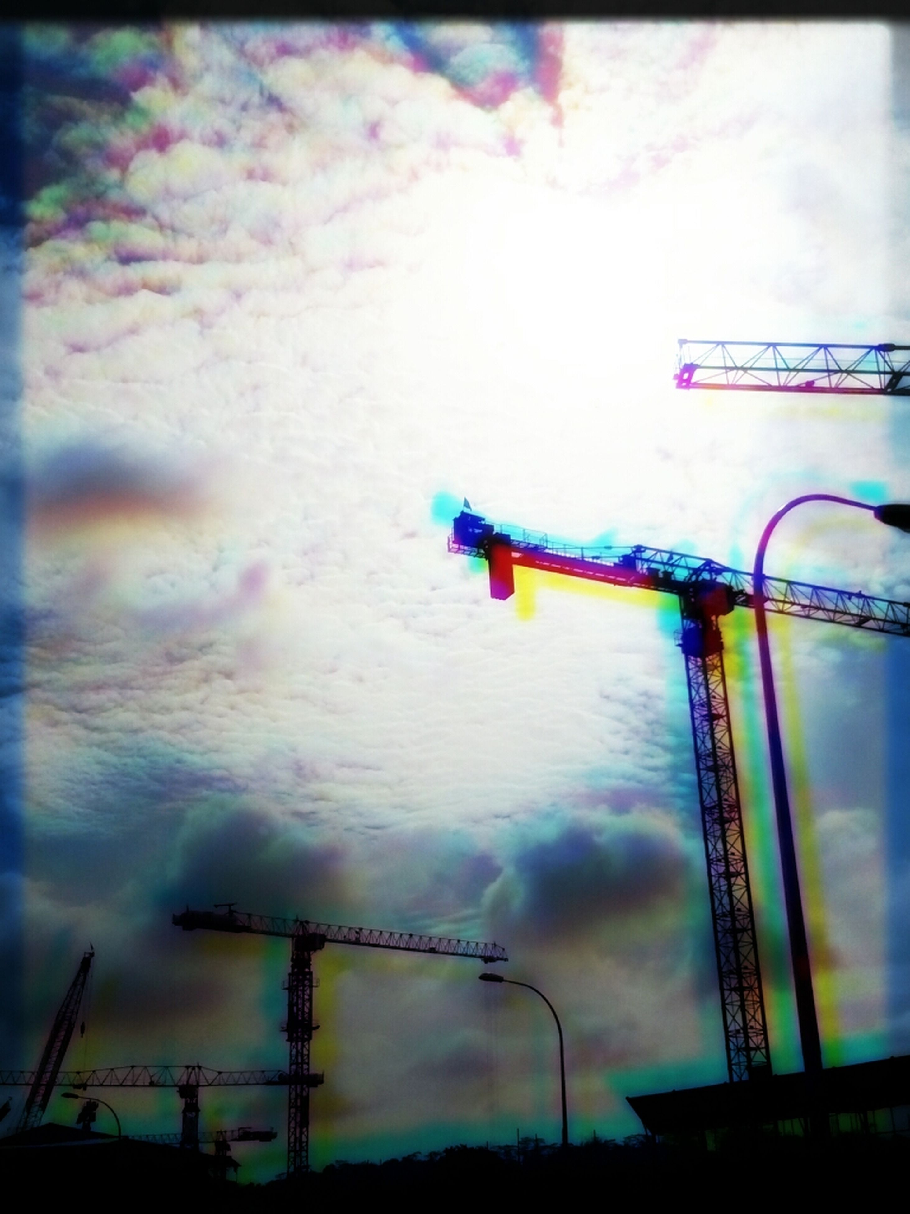 low angle view, sky, auto post production filter, transfer print, cloud - sky, dusk, built structure, metal, outdoors, communication, no people, cloudy, cloud, construction site, silhouette, lighting equipment, electricity, connection, architecture, fence
