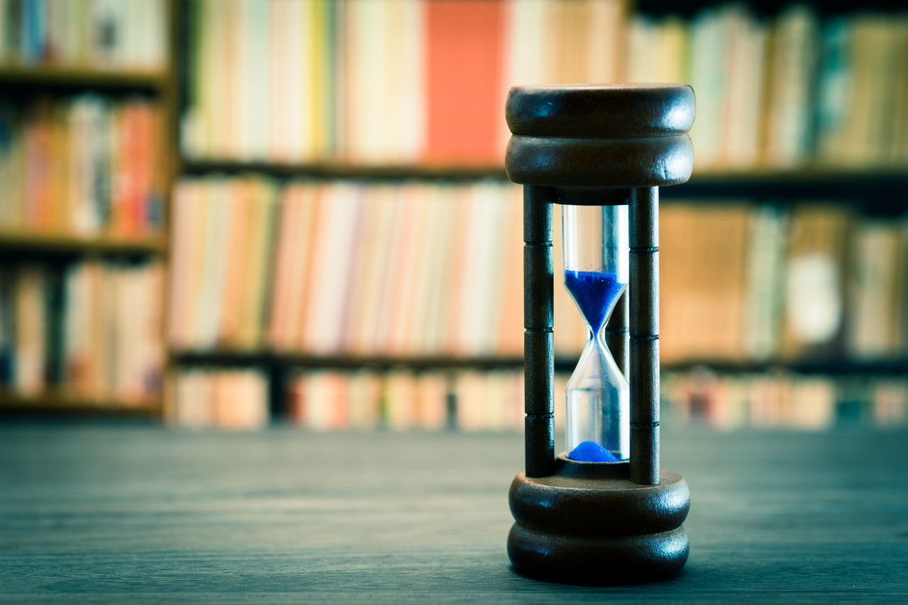 Hourglass against bookshelf Book Business Deadline Deal Desk Hourglass Hurry Knowledge Learn Limit Money Office Paperwork Reading Sandglass Secondeyeemphoto Study Time Time Is Money Trade Work