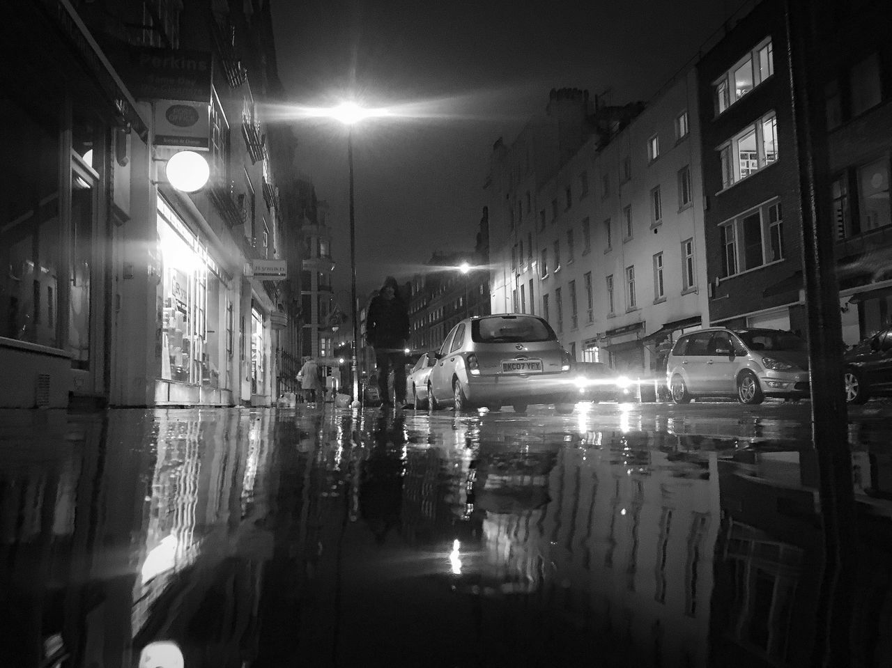 illuminated, night, building exterior, architecture, street, street light, built structure, outdoors, road, no people, city, light beam, water, puddle, sky