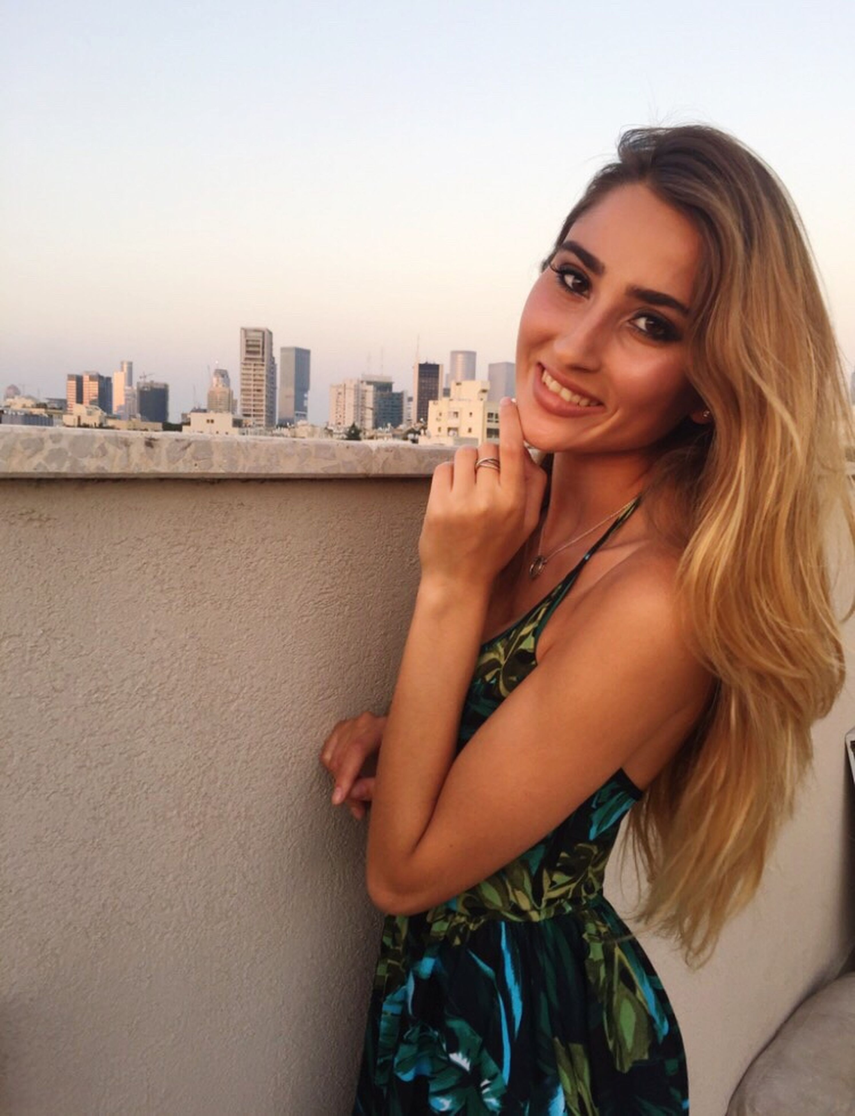 smiling, portrait, long hair, one person, city, architecture, built structure, looking at camera, fashion, beautiful woman, beauty, happiness, blond hair, building exterior, skyscraper, beautiful people, young adult, fashion model, real people, outdoors, standing, cityscape, modern, young women, day, sky, adult, people, adults only