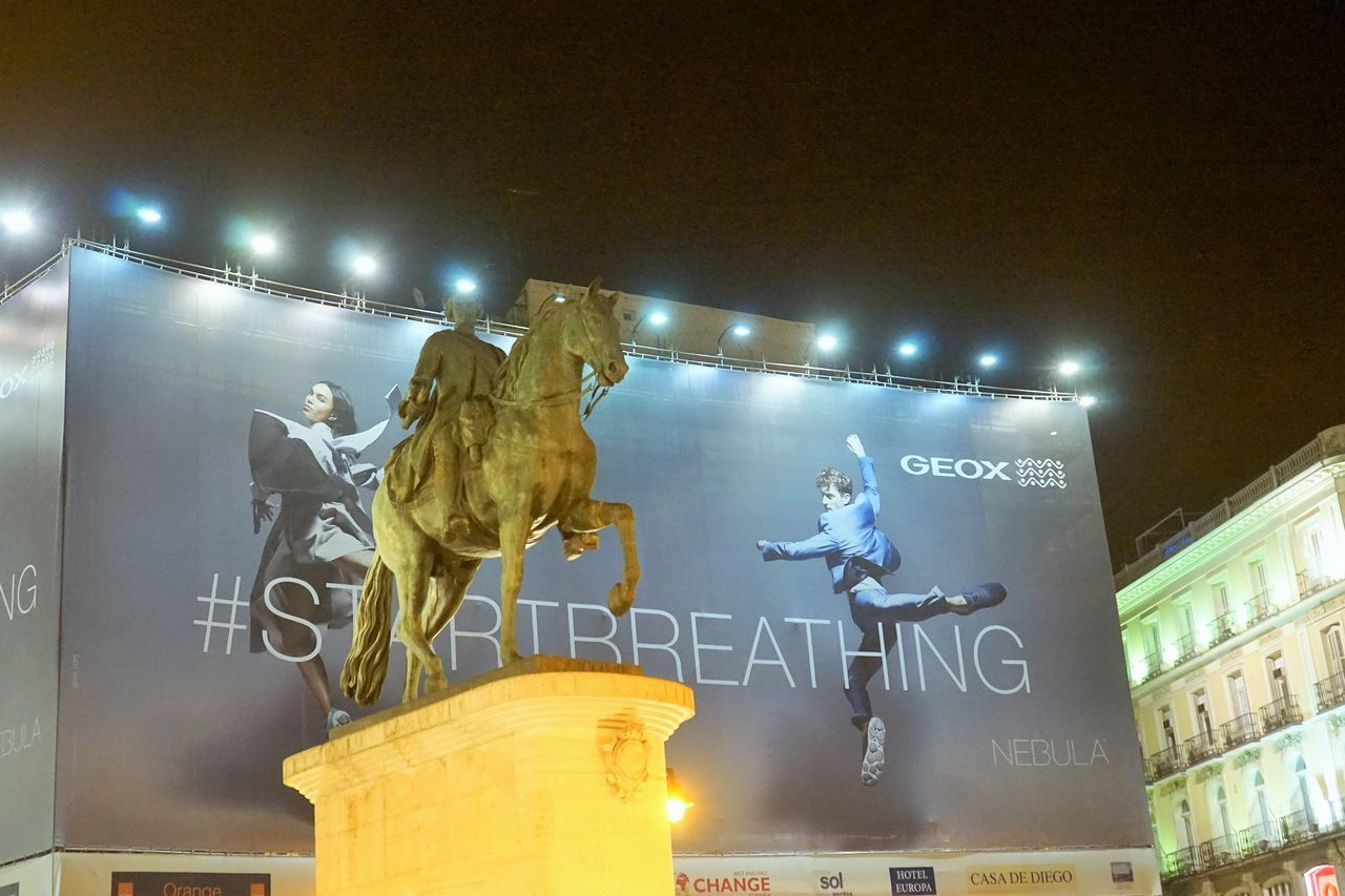 horse, night, male likeness, illuminated, human representation, text, statue, built structure, low angle view, men, arts culture and entertainment, architecture, sculpture, outdoors, real people, people