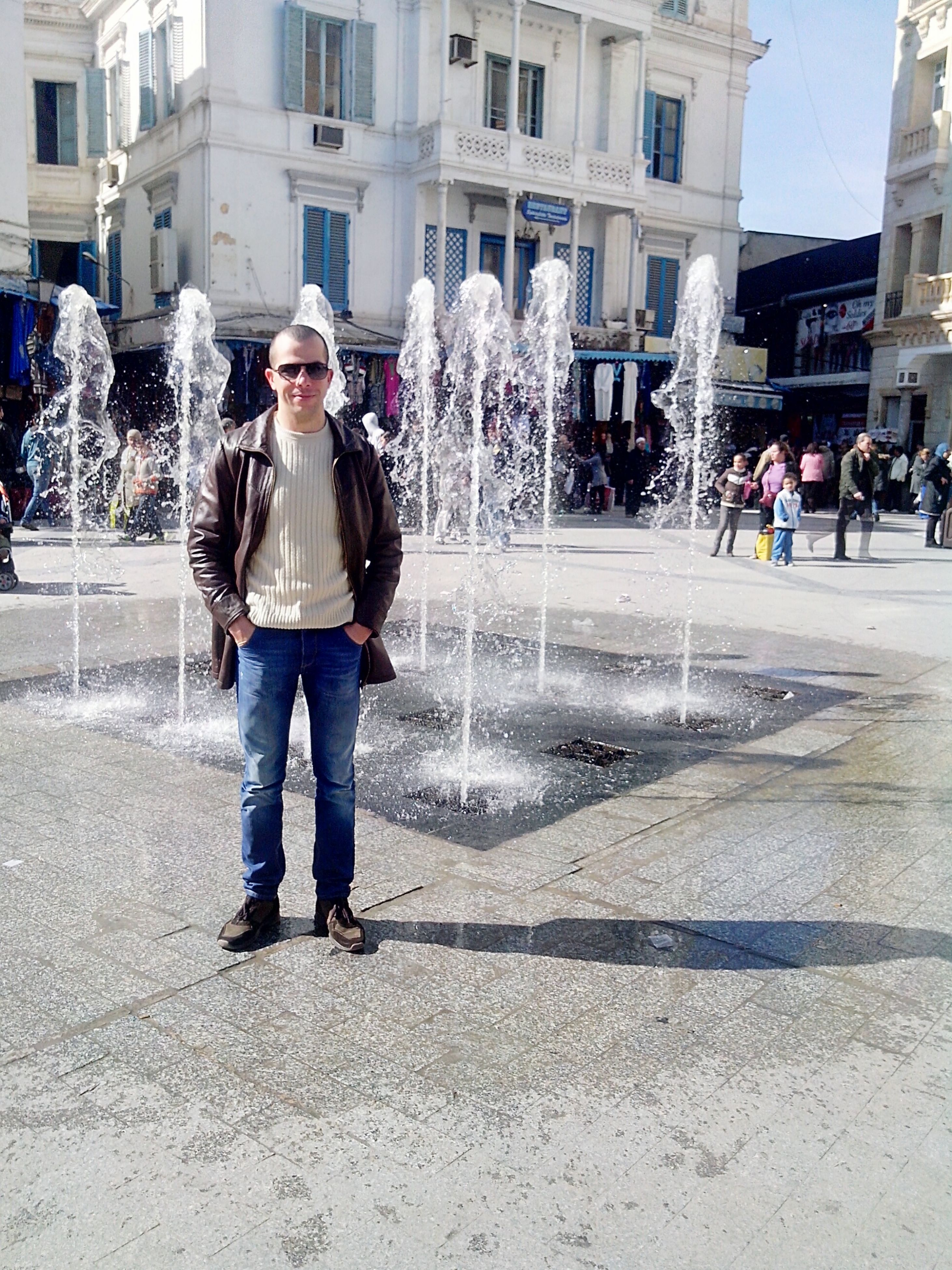 building exterior, architecture, built structure, lifestyles, fountain, leisure activity, city, street, person, men, large group of people, city life, full length, motion, walking, incidental people, casual clothing, spraying