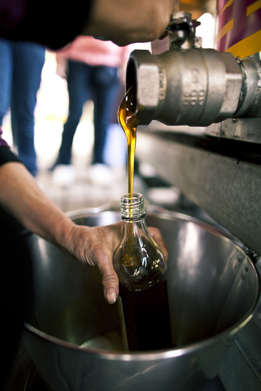 Close-Up Of Hand Bottling Honey