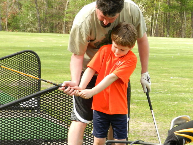 Golf lessons Casual Clothing Childhood Driving Range Father And Son Time Fatherhood Moments Fatherhood Moments By September 8 2016 Golf Golfing Lessons Green Grip Hand Holding Innocence Leisure Activity Orange Outdoors Person Teachable Moment Togetherness Tree