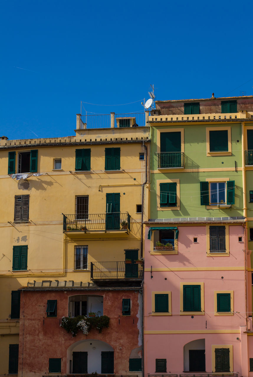 architecture, building exterior, urban, built structure, building, town, city, place, window, exterior, residential, residential building, blue, no people, outdoors, yellow, clear sky, day, sky