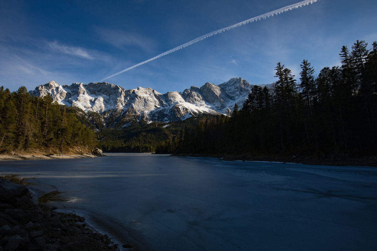 Alps Bavaria Beauty In Nature Blue Sky Cold Temperature Day Eibsee Germany Landscape Mountain Mountain Range Nature No People Outdoors Scenics Sky Snow Tree Vacation Vapor Trail Water Zugspitze Travel