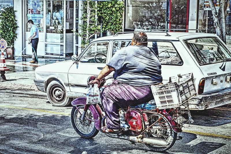 Urban Street Scene Street Life Big Man On A Small Bike In The Foreground Delivery Heroes Light And Shadow Sunny Day Light Colors Hot Summer Day Alanya Turkey Showcase July People Together