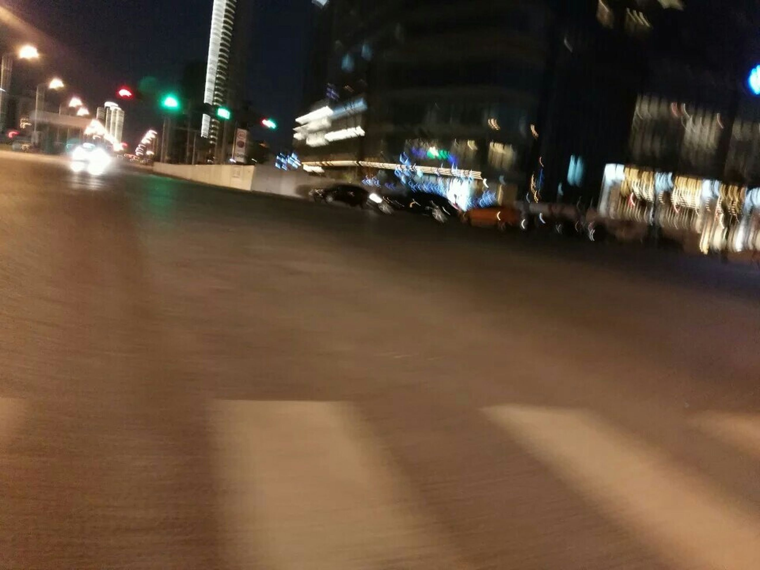 illuminated, night, transportation, city, mode of transport, street, building exterior, architecture, land vehicle, built structure, city life, car, city street, street light, road, incidental people, lighting equipment, traffic, on the move, travel