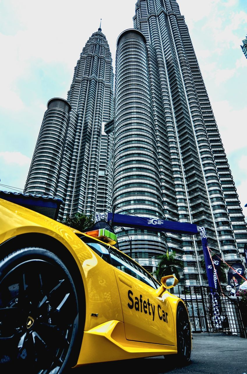 transportation, car, architecture, land vehicle, mode of transport, skyscraper, taxi, built structure, building exterior, city, yellow taxi, outdoors, sky, travel, modern, yellow, day, travel destinations, no people