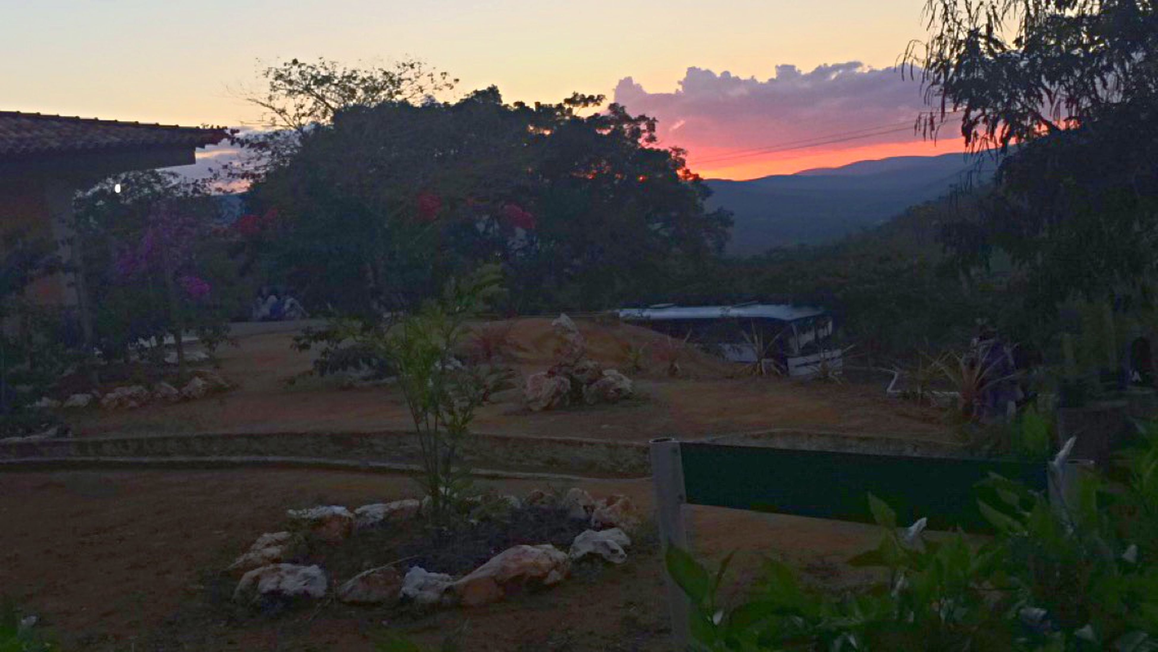 tree, sunset, mountain, tranquil scene, beauty in nature, tranquility, scenics, sky, nature, orange color, growth, built structure, idyllic, rock - object, house, landscape, dusk, outdoors, non-urban scene, no people
