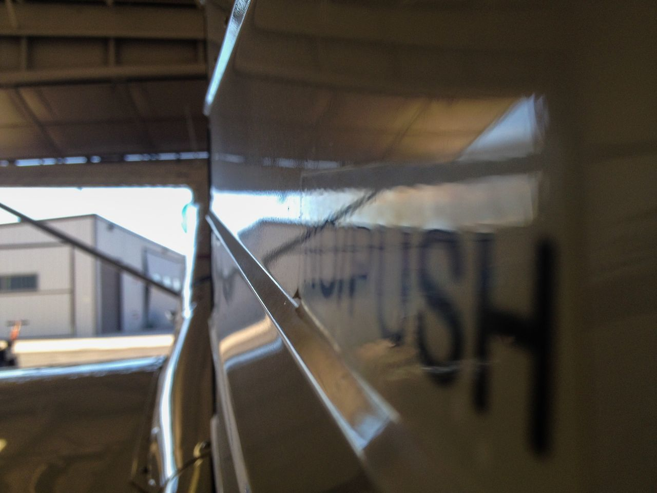 Sign on the tail of an Aircraft warning you not to Push it. Reflection Reflections Hangar