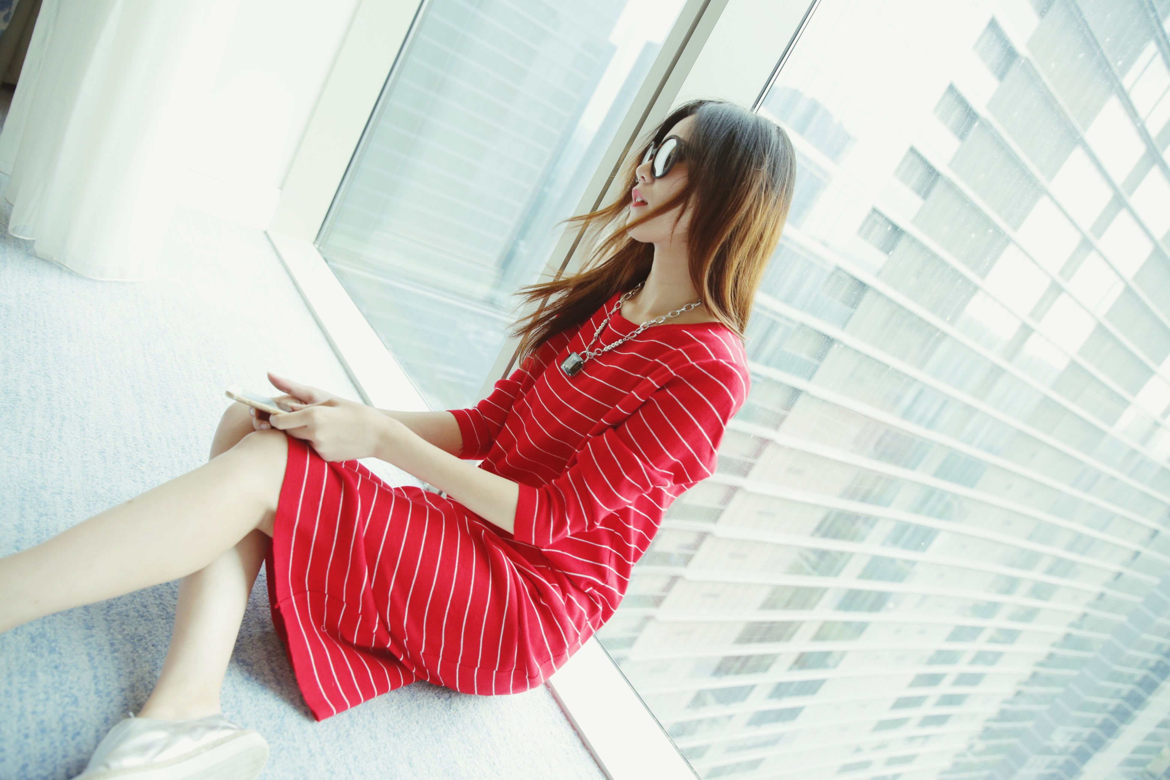 indoors, lifestyles, young women, young adult, red, home interior, sensuality, femininity, person, leisure activity, casual clothing, dress, holding, curtain, sitting, long hair