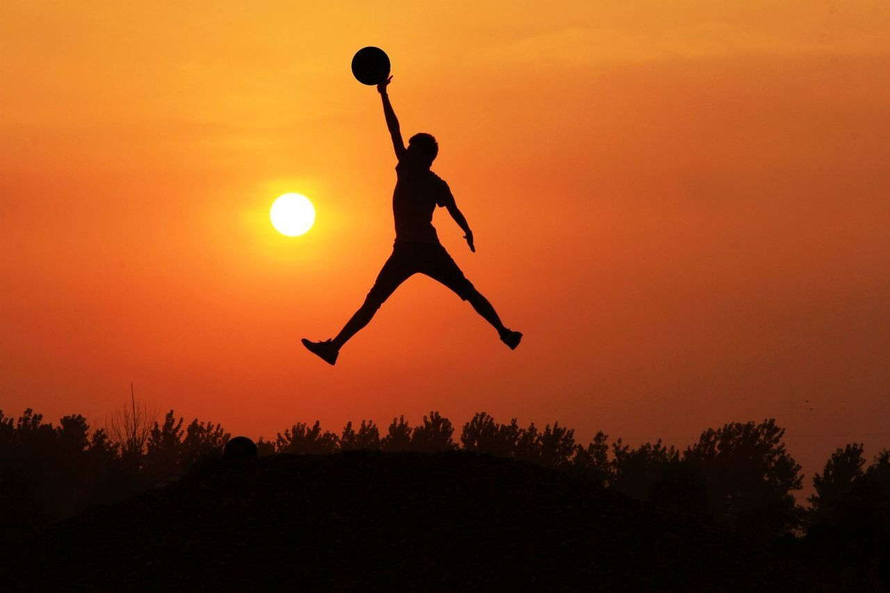 Midsection Of Silhouette Man Catching Ball In Mid-Air Against Orange Sky